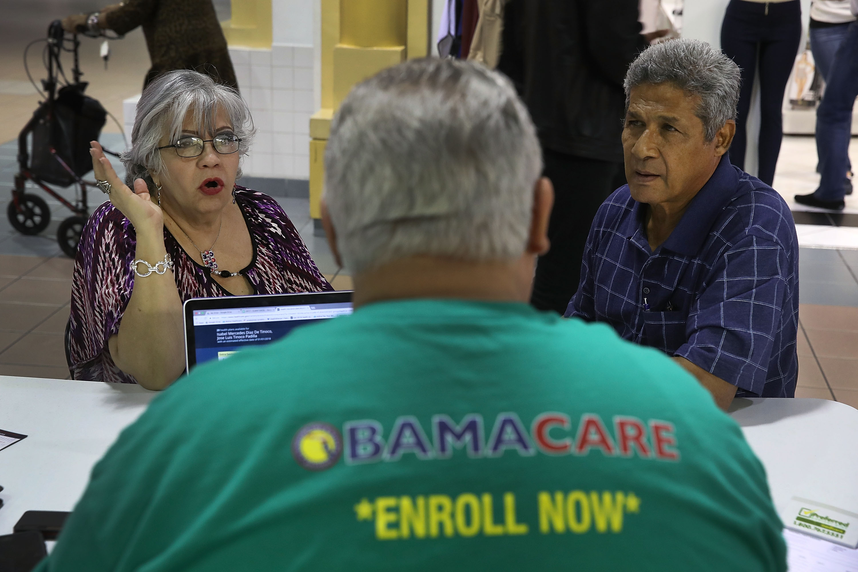 Isabel Diaz Tinoco (L) and Jose Luis Tinoco speak with Otto Hernandez, an insurance agent from Sunshine Life and Health Advisors, as they shop for insurance under the Affordable Care Act at a store setup in the Mall of Americas on November 1, 2017 in Miami, Florida. (Photo by Joe Raedle/Getty Images)