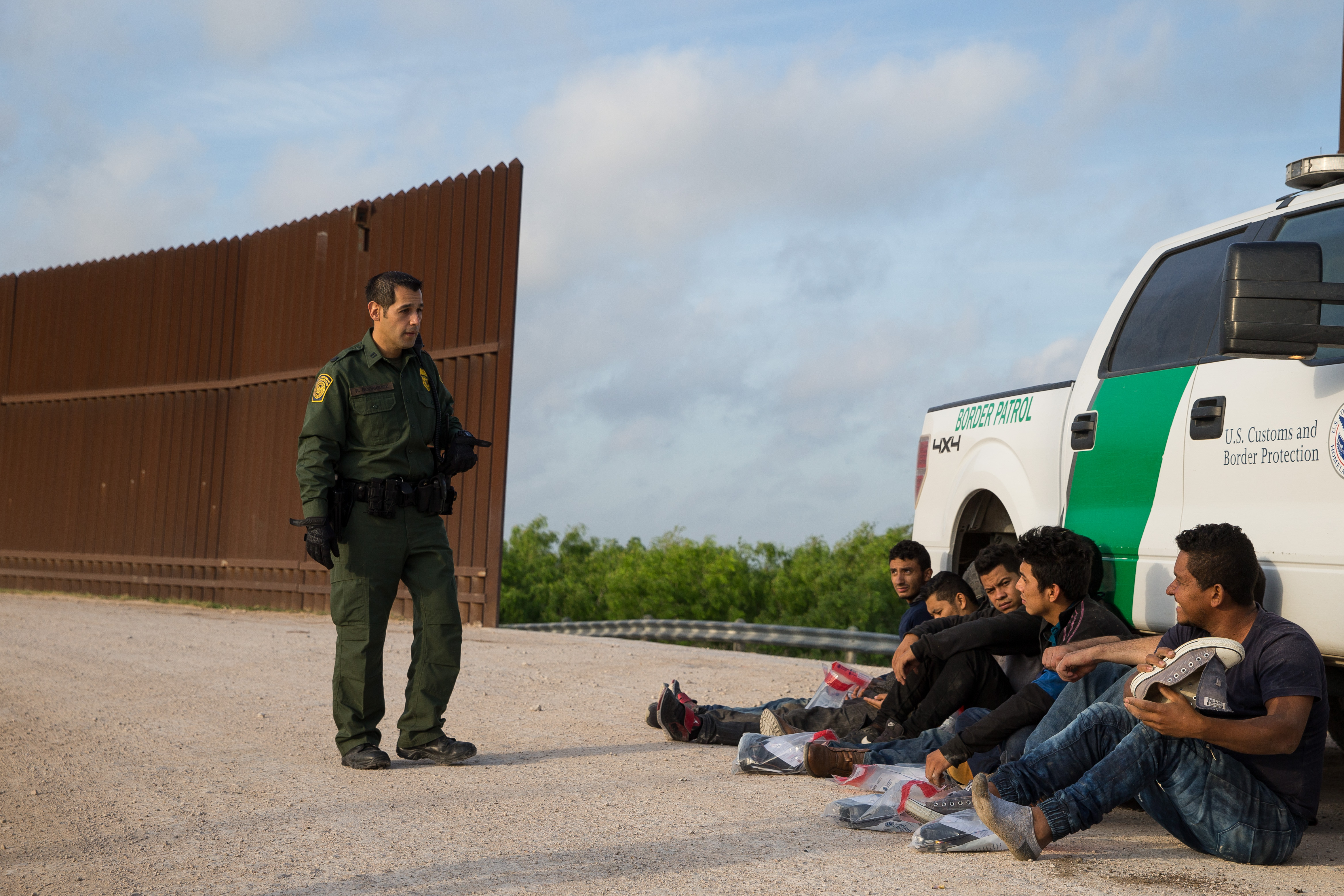 A Border Patrol agent apprehends illegal immigrants shortly after they crossed the border from Mexico into the United States on Monday, March 26, 2018. (Photo credit should read LOREN ELLIOTT/AFP/Getty Images)