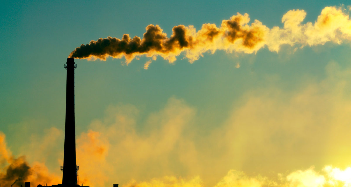 Steam rises from a smokestack on a factory silhouetted against the sunlight. Shutterstock