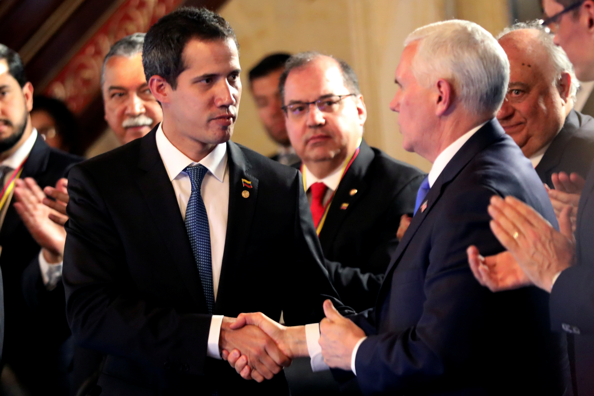 U.S. Vice President Mike Pence and Venezuelan opposition leader Juan Guaido, who many nations have recognized as the country's rightful interim ruler, shake hands during a meeting of the Lima Group in Bogota, Colombia, February 25, 2019. REUTERS/Luisa Gonzalez
