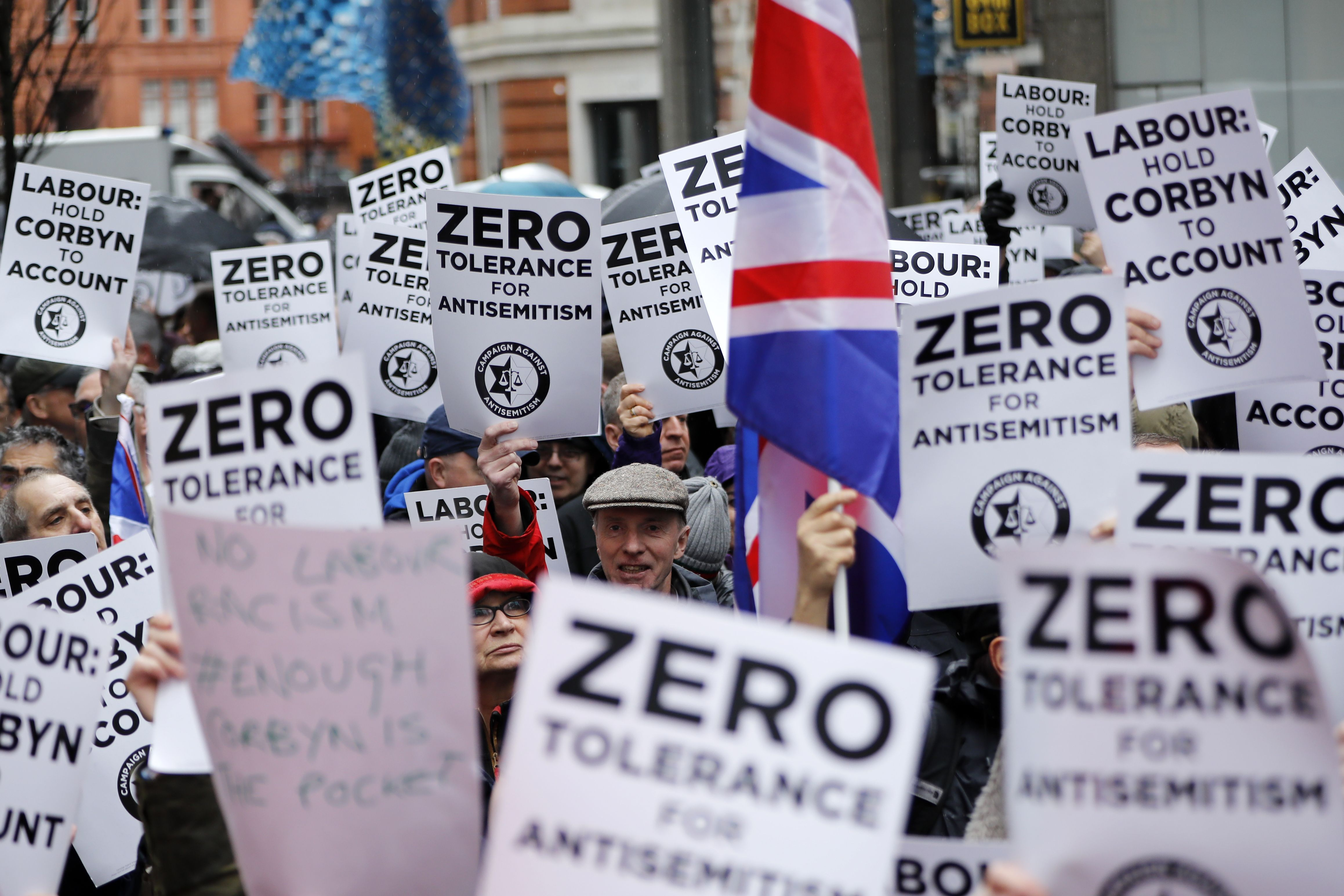 People hold up placards and Union flags as they gather for a demonstration organised by the Campaign Against Anti-Semitism outside the office of the Labour Party. Labour leader Jeremy Corbyn has been under increasing pressure to address multiple allegations of anti-Semitism within the party. (Tolda Akmen/AFP/Getty Images)