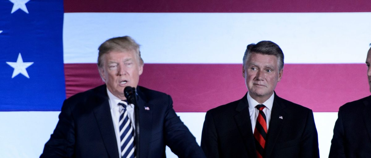 US House candidate from North Carolina Mark Harris (C) and Rep. Ted Budd (R) listen to US President Donald Trump speech during a fundraiser at the Carmel Country Club August 31, 2018 in Charlotte, North Carolina. (BRENDAN SMIALOWSKI/AFP/Getty Images)