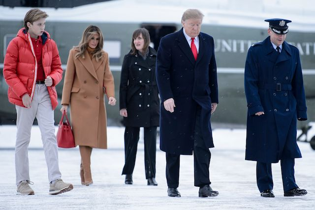 US President Donald Trump, US first lady Melania Trump and son Barron Trump walk the snowy tarmac to Air Force One at Andrews Air Force Base February 1, 2019 in Maryland, en route to Palm Beach, Florida.(Photo credit: BRENDAN SMIALOWSKI/AFP/Getty Images)
