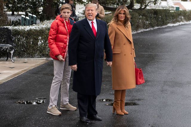 US President Donald Trump (C) shouts to the press as he departs the White House in Washington, DC, on February 1, 2019, with First Lady Melania Trump (R) and his son Barron (L), en route to Palm Beach, Florida. (Photo credit: JIM WATSON/AFP/Getty Images)