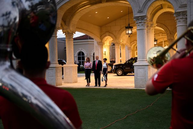 US President Donald Trump and US first lady Melania Trump listen to the Florida Atlantic University band at the Trump International Golf Club before a Super Bowl party February 3, 2019 in West Palm Beach, Florida. (Photo credit: BRENDAN SMIALOWSKI/AFP/Getty Images)