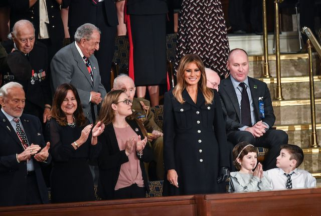 First Lady Melania Trump (C) is greeted, surrounded by special guests of the President (including Buzz Aldrin on L), as she arrives for US President Donald Trump's State of the Union address at the US Capitol in Washington, DC on February 5, 2019. (Photo credit: MANDEL NGAN/AFP/Getty Images)