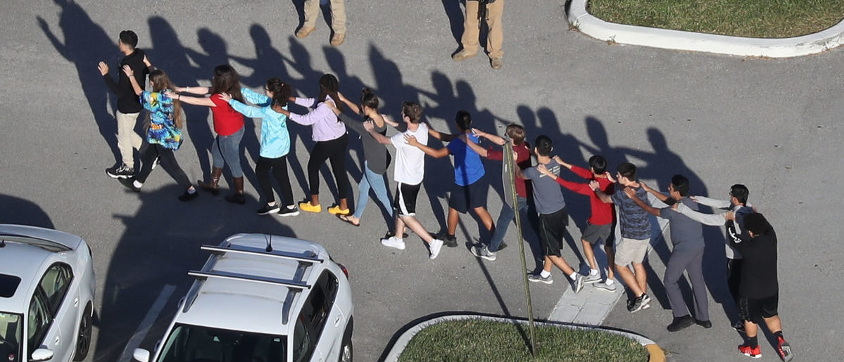 People are brought out of the Marjory Stoneman Douglas High School after a shooting at the school that reportedly killed and injured multiple people on Feb. 14, 2018 in Parkland, Florida. Getty Images/ Joe Raedle