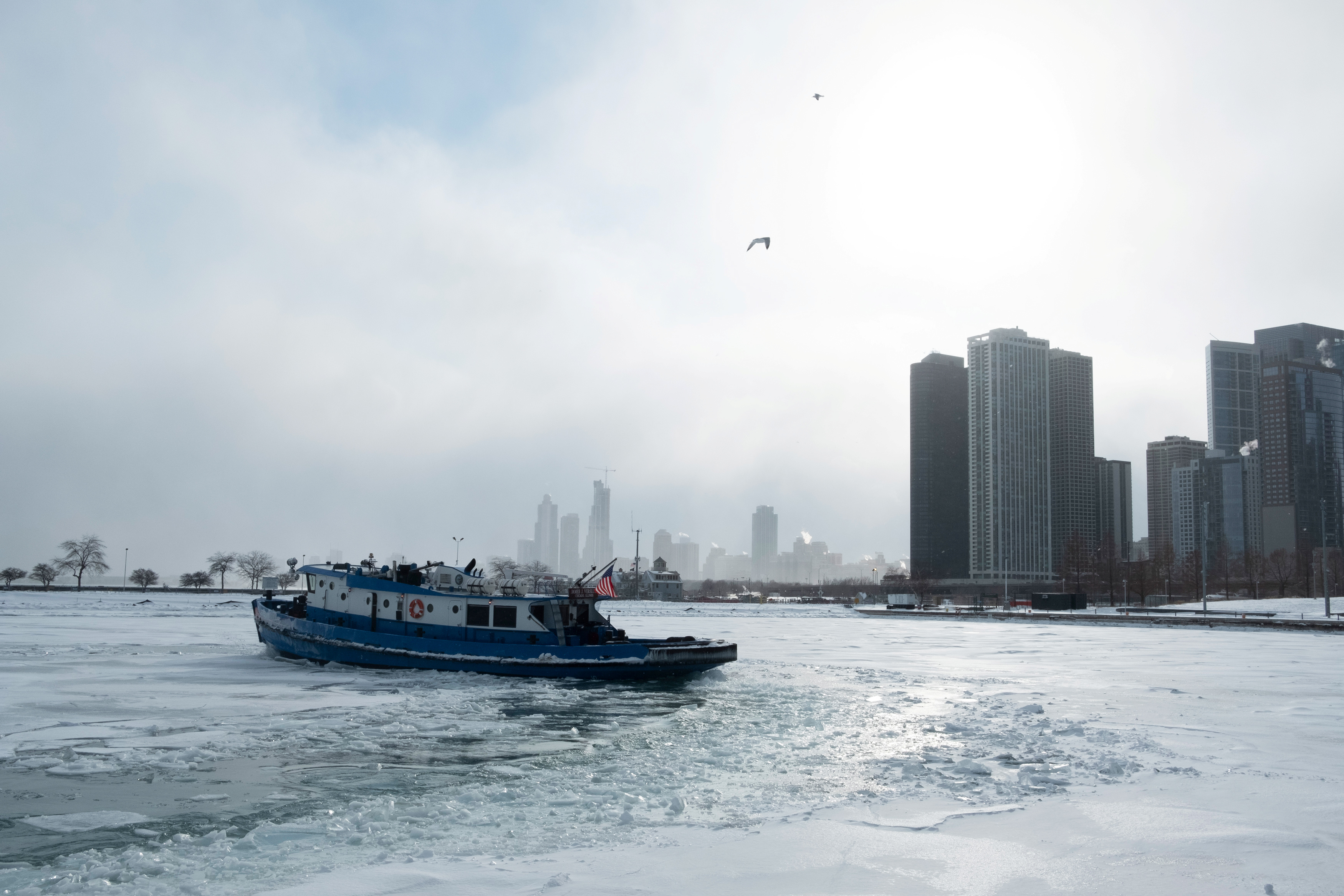 Icebreaker tugboat breaks ice through Lake Michigan in Chicago