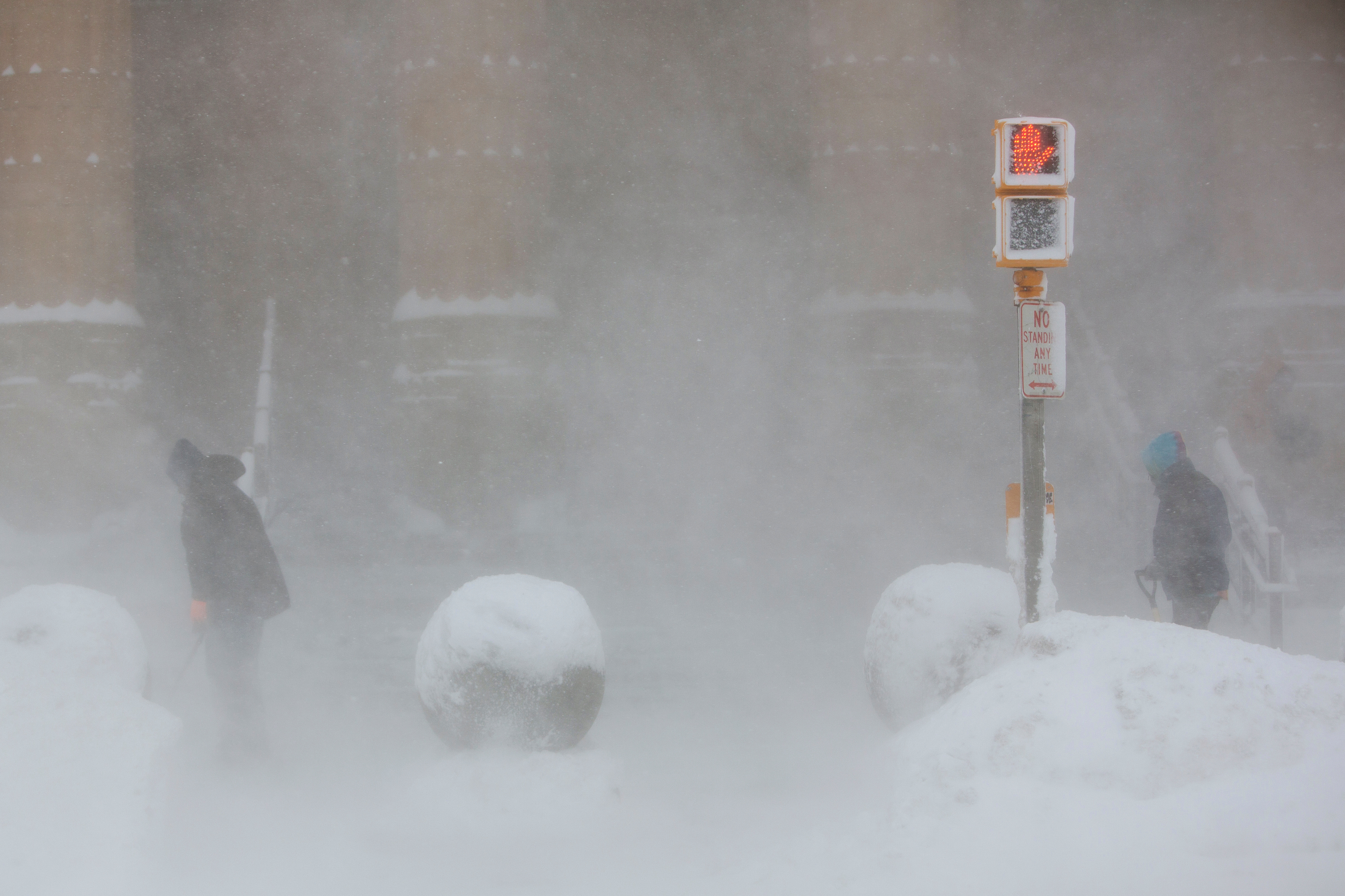 Workers shovel at the entrance to City Hall in whiteout conditions during winter storm in Buffalo, NY