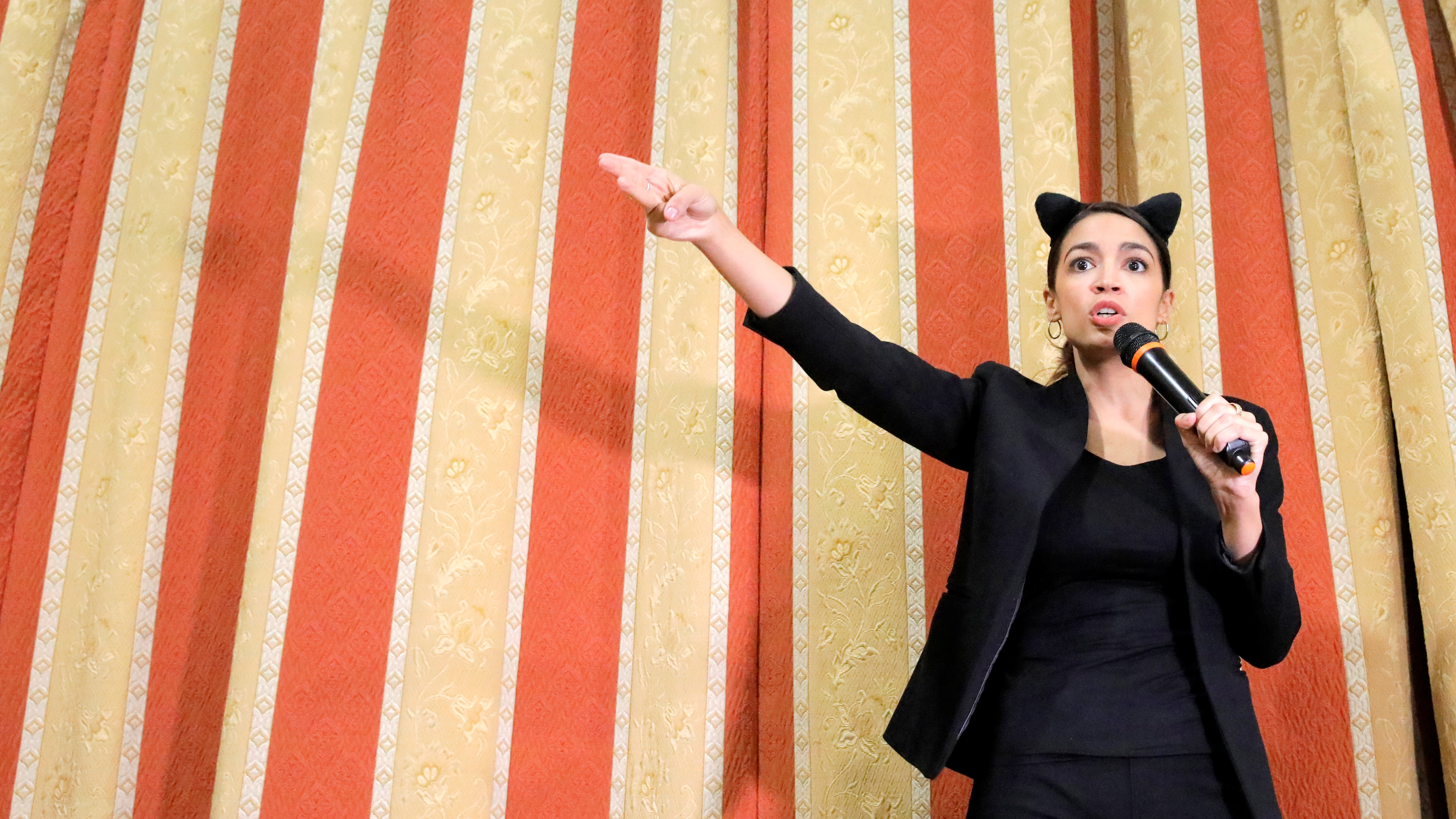 "Democratic Congressional candidate Alexandria Ocasio-Cortez delivers remarks in her costume as a bodega cat while she attends the ""Halloween with Alexandria"" event at St Paul's Evangelical Lutheran Church in the Bronx, New York"