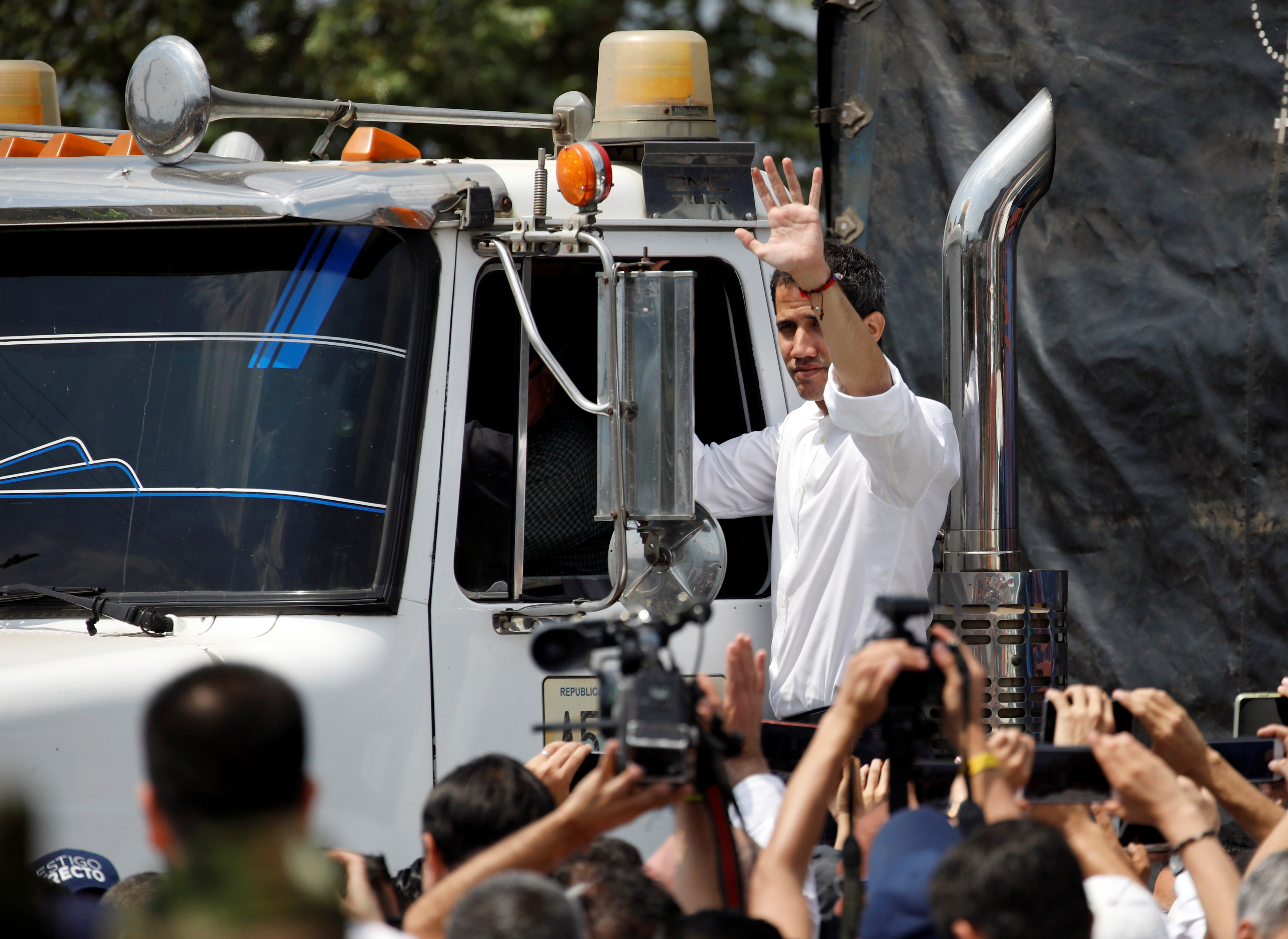 Venezuelan opposition leader Juan Guaido, who many nations have recognized as the country's rightful interim ruler gestures while standing on a truck carrying humanitarian aid for Venezuela in the area of a warehouse where humanitarian aid for Venezuela has been collected in Cucuta, Colombia, February 23, 2019. REUTERS/Marco Bello