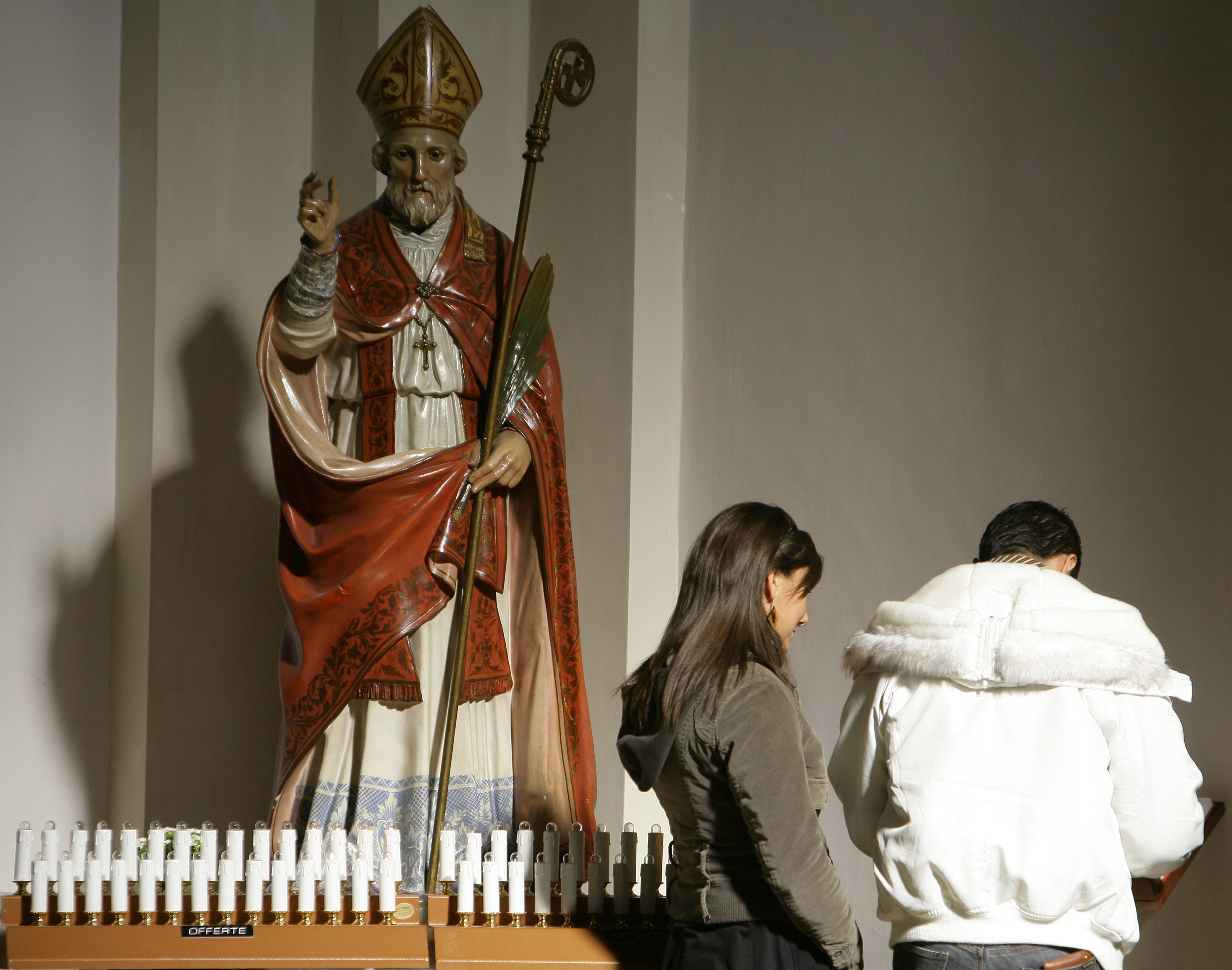 A couple stands in front of the St.Valentine's statue inside the St. Valentine Basilica in Terni, Umbria, February 10, 2008. REUTERS/Daniele La Monaca (ITALY)