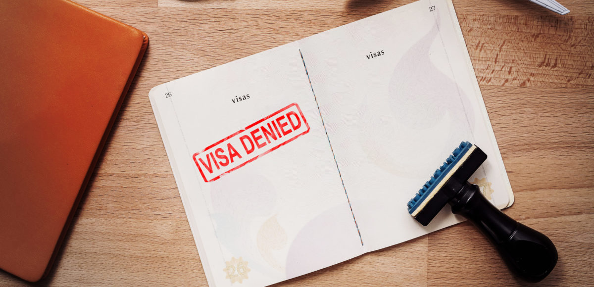 Visa and passport with denied stamp on a document top view in immigration. Shutterstock