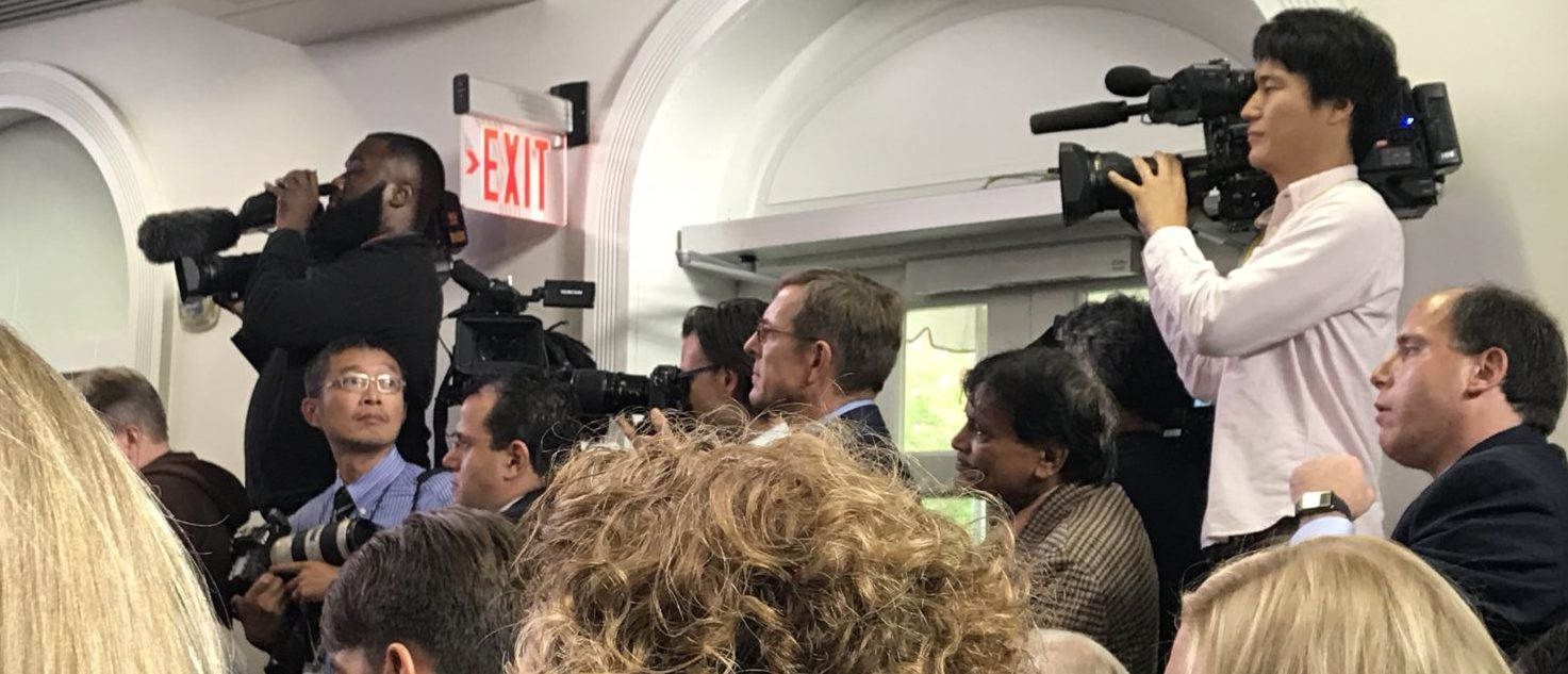 White House reporters gather for a briefing. They'll step over one another to get a good shot.