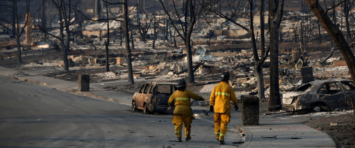 FILE PHOTO: Firefighters walk in a neighborhood destroyed by the Tubbs Fire in Santa Rosa, California, U.S., October 13, 2017. REUTERS/Stephen Lam/File Photo