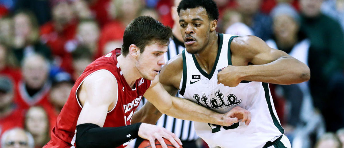 MADISON, WISCONSIN - FEBRUARY 12: Ethan Happ #22 of the Wisconsin Badgers dribbles the ball while being guarded by Xavier Tillman #23 of the Michigan State Spartans in the second half at the Kohl Center on February 12, 2019 in Madison, Wisconsin. (Photo by Dylan Buell/Getty Images)