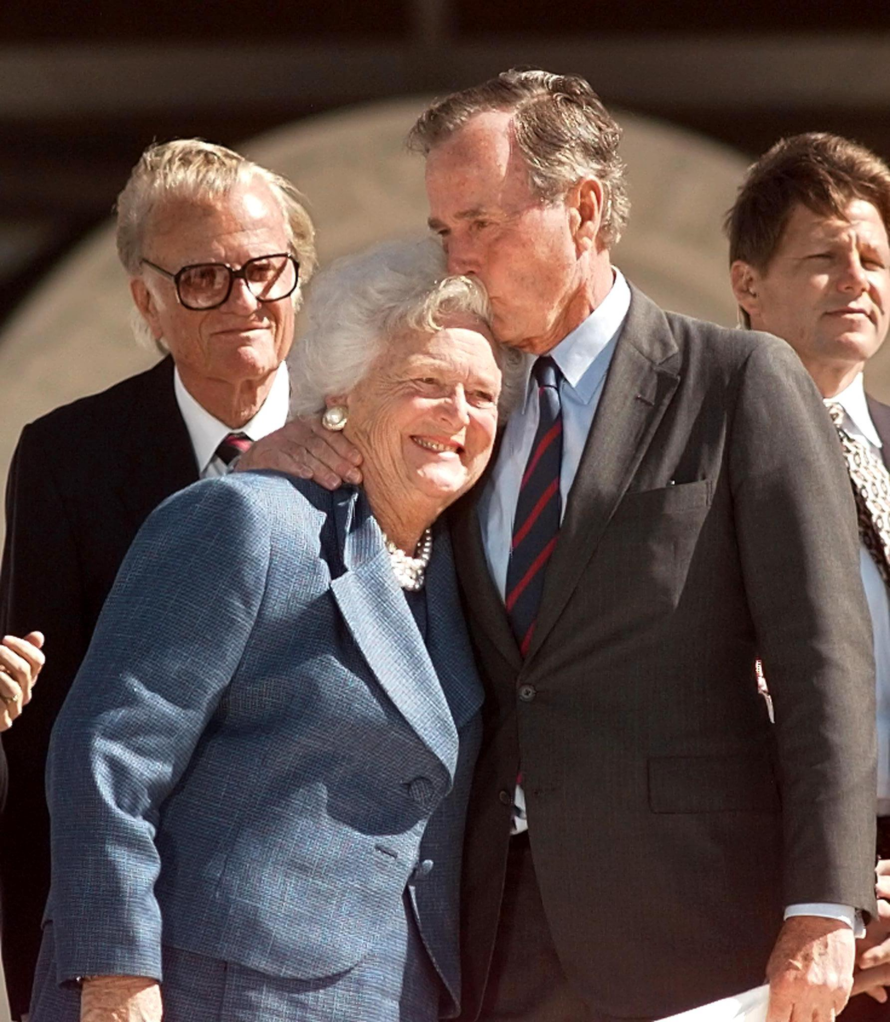 Former President George Bush kisses his wife Barbara as preacher Billy Graham looks on at the dedication ceremony of the George Bush Library. (Joyce Naltchayan/AFP/Getty Images)