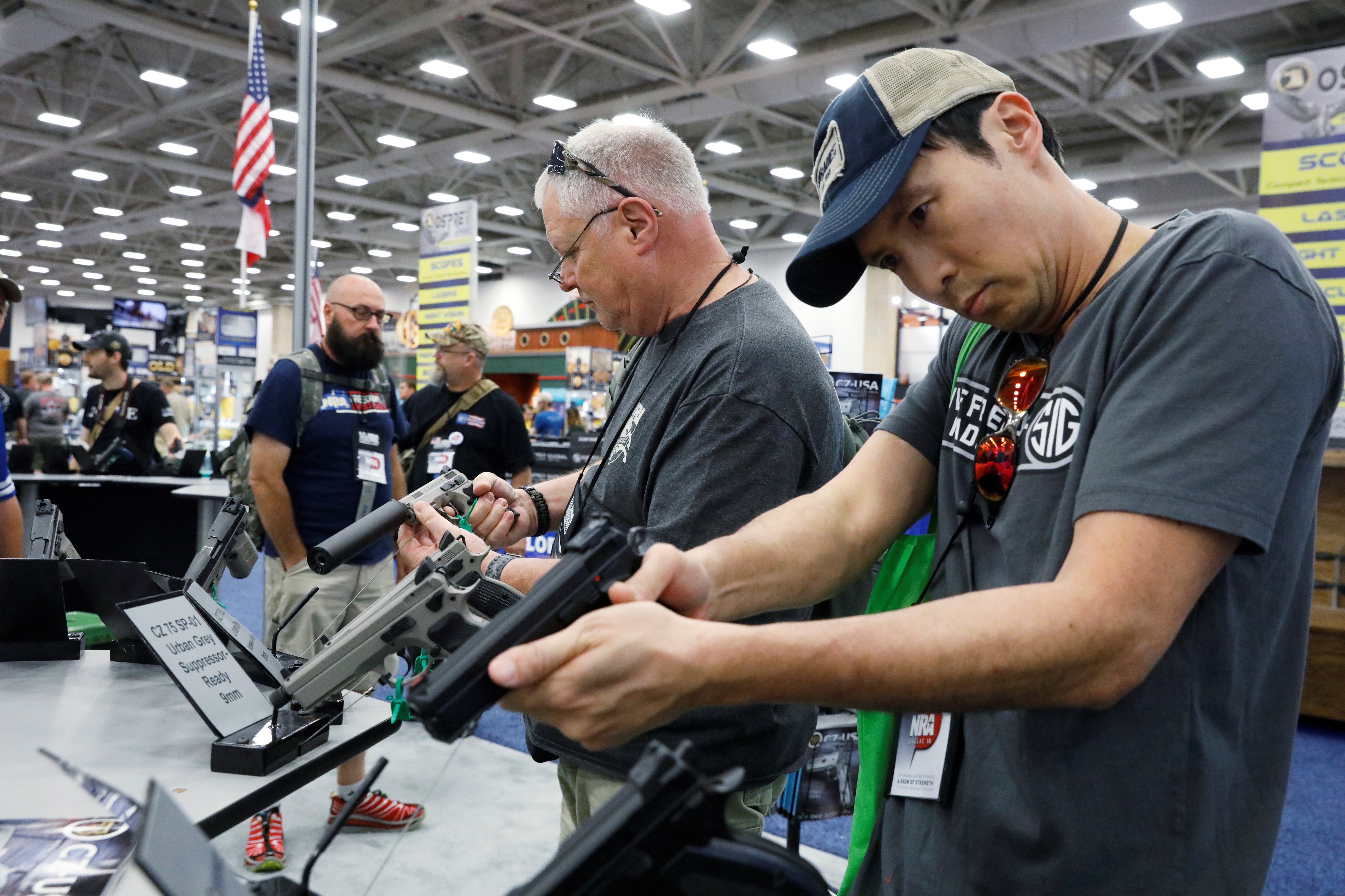 Gun enthusiasts inspect firearms during the annual National Rifle Association (NRA) convention in Dallas, Texas, U.S., May 5, 2018. REUTERS/Lucas Jackson