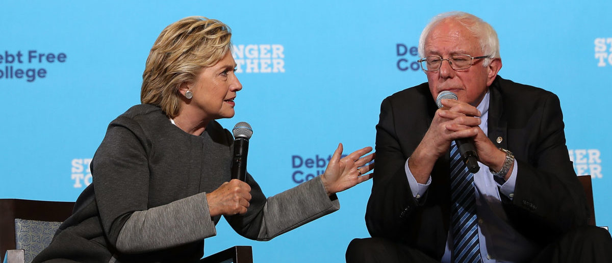Democratic presidential nominee former Secretary of State Hillary Clinton (L) speaks as U.S. Sen. Bernie Sanders (I-VT) looks on during a campaign rally at University of New Hampshire on September 28, 2016 in Durham, New Hampshire. (Photo by Justin Sullivan/Getty Images)
