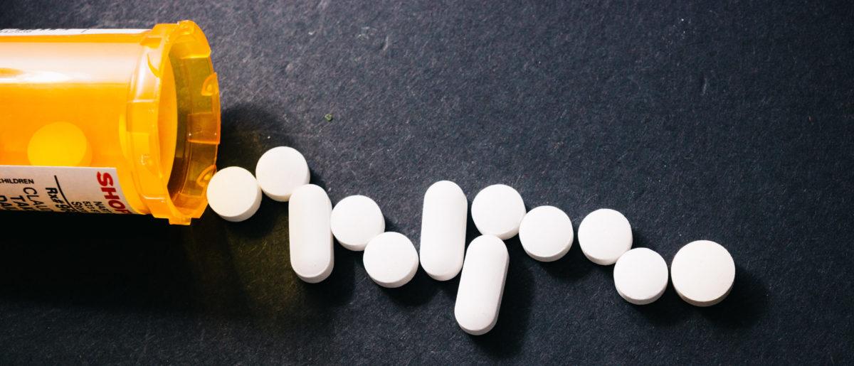Pills spill out of a bottle. Shutterstock image via user video_creative