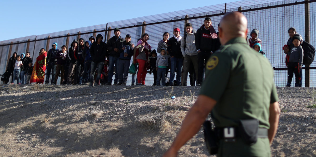 A group of Central American migrants surrenders to U.S. Border Patrol Agent Jose Martinez south of the U.S.-Mexico border fence in El Paso