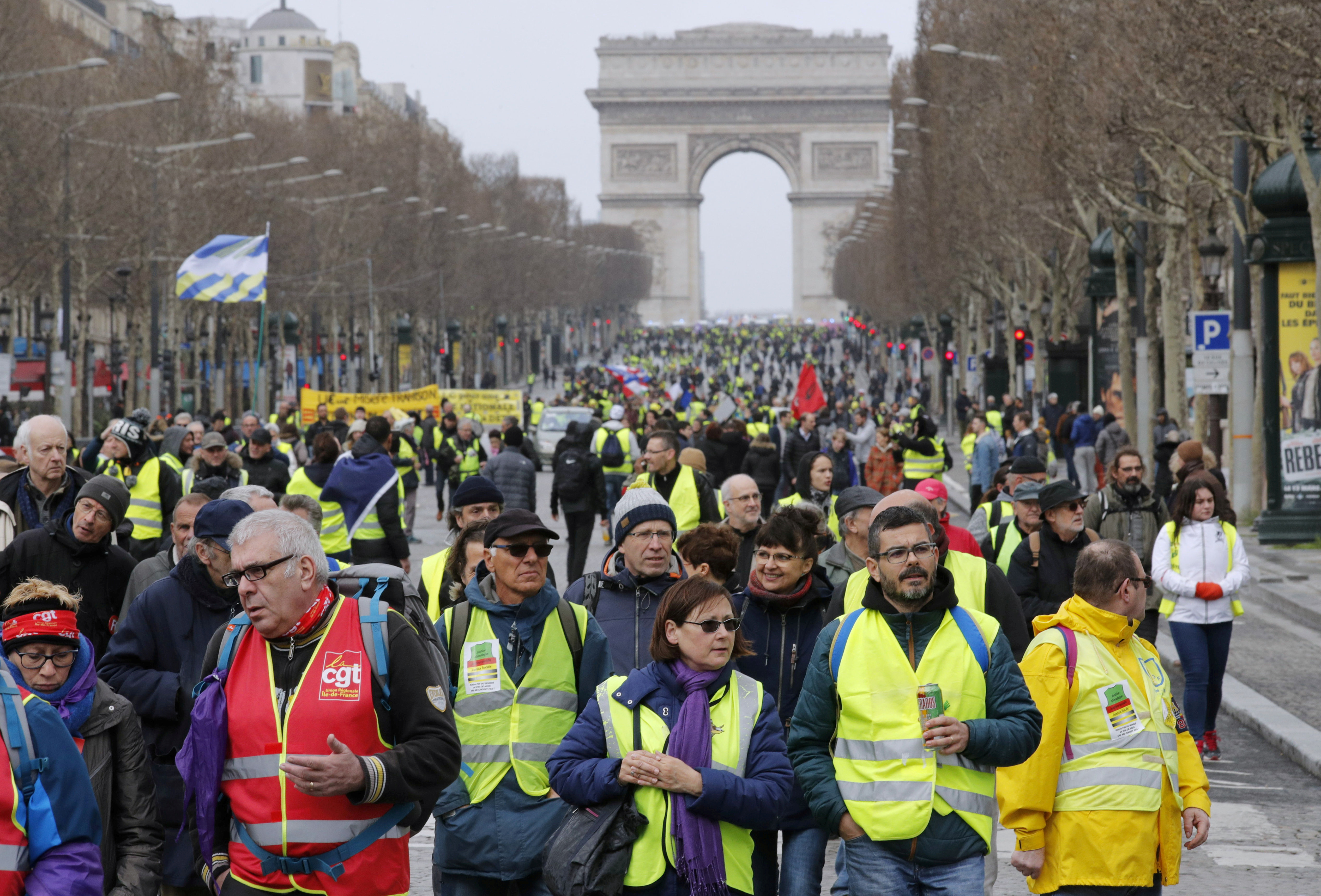 "Protesters wearing yellow vests walk down the Champs Elysees during a demonstration by the ""yellow vests"" movement in Paris, France, March 9, 2019. REUTERS/Philippe Wojazer"