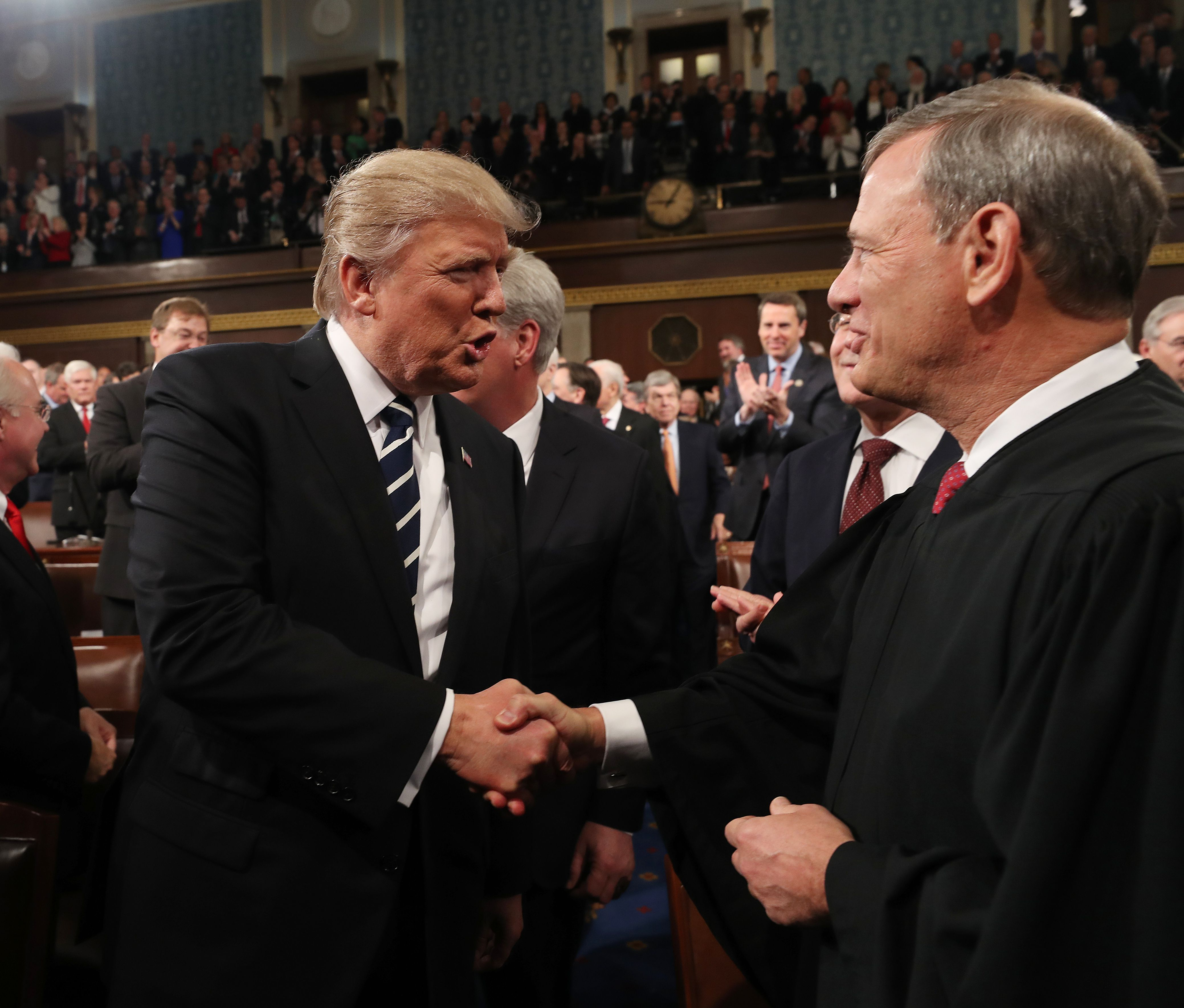 President Donald Trump shakes hands with Chief Justice John Roberts as he arrives to deliver his first address to a joint session of Congress from the floor of the House of Representatives in February 2017. (Jim Lo Scalzo/AFP/Getty Images)