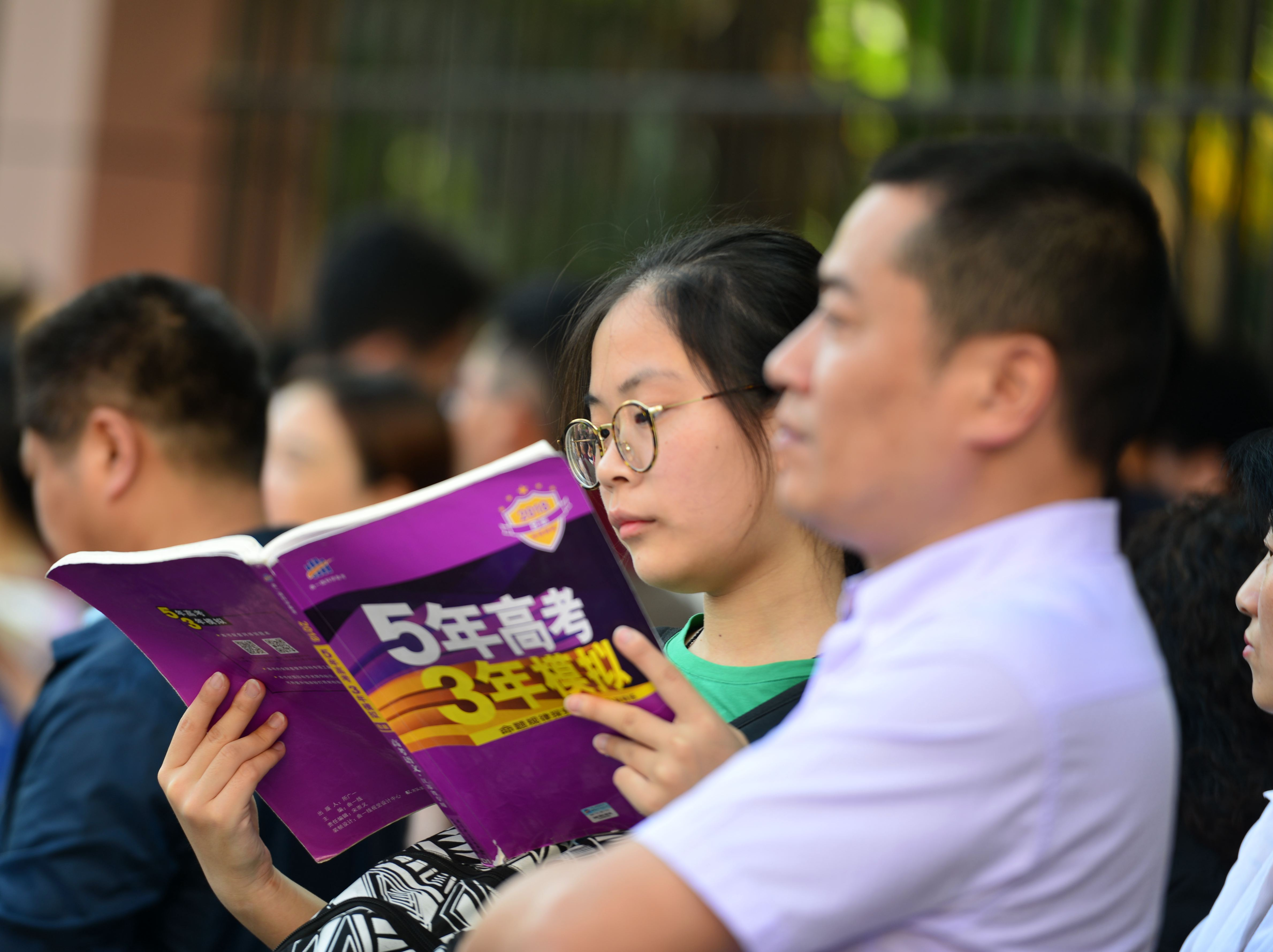 A candidate reviews before entering an exam site for the National College Entrance Examination (aka Gaokao) at Nanjing No.29 High School on June 7, 2018 in Nanjing, Jiangsu Province of China. (Photo by VCG/VCG via Getty Images)