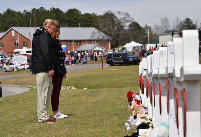 US President Donald Trump and First Lady Melania Trump stand before a row of crosses honoring 23 people who died in the storm outside Providence Baptist Church March 8, 2019 in Opelika, Alabama, during a tour of tornado-damaged areas in the southern US state. (Photo credit: NICHOLAS KAMM/AFP/Getty Images)