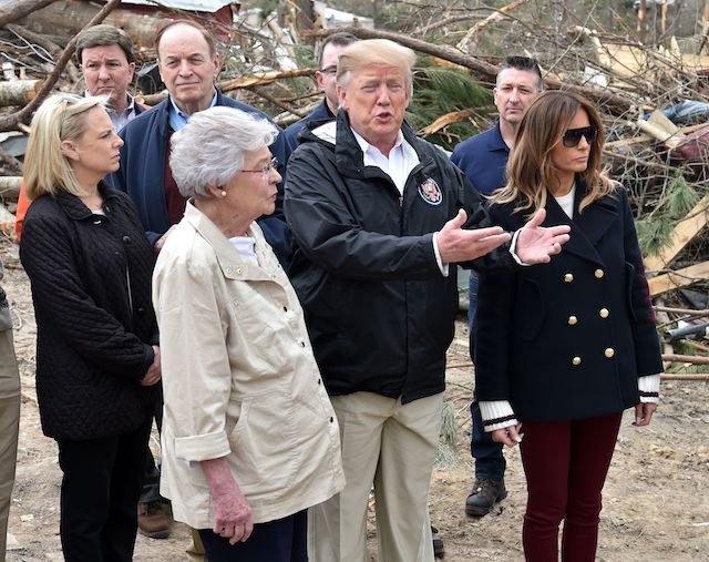 US President Donald Trump (C) and First Lady Melania Trump (R) tour of tornado-affected areas with Homeland Security Secretary Kirstjen Nielsen (L front), Senator Richard Shelby (2nd L) and Governor Kay Ivey on March 8, 2019 in Beauregard, Alabama. (Photo credit: NICHOLAS KAMM/AFP/Getty Images)