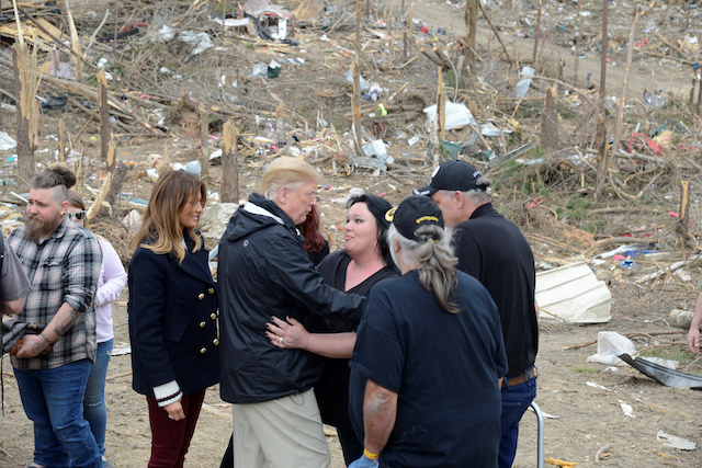 U.S. President Donald Trump is hugged by a resident who survived a tornado, as First Lady Melania Trump stands by, in Beauregard, Alabama, U.S., March 8, 2019. REUTERS/Mike Theiler