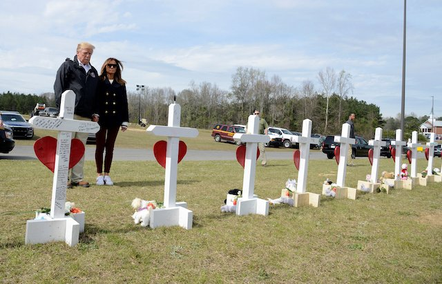 U.S. President Donald Trump and First Lady Melania Trump pause at a row of crosses for the victims of a tornado in Beauregard, Alabama, U.S., March 8, 2019. REUTERS/Mike Theiler