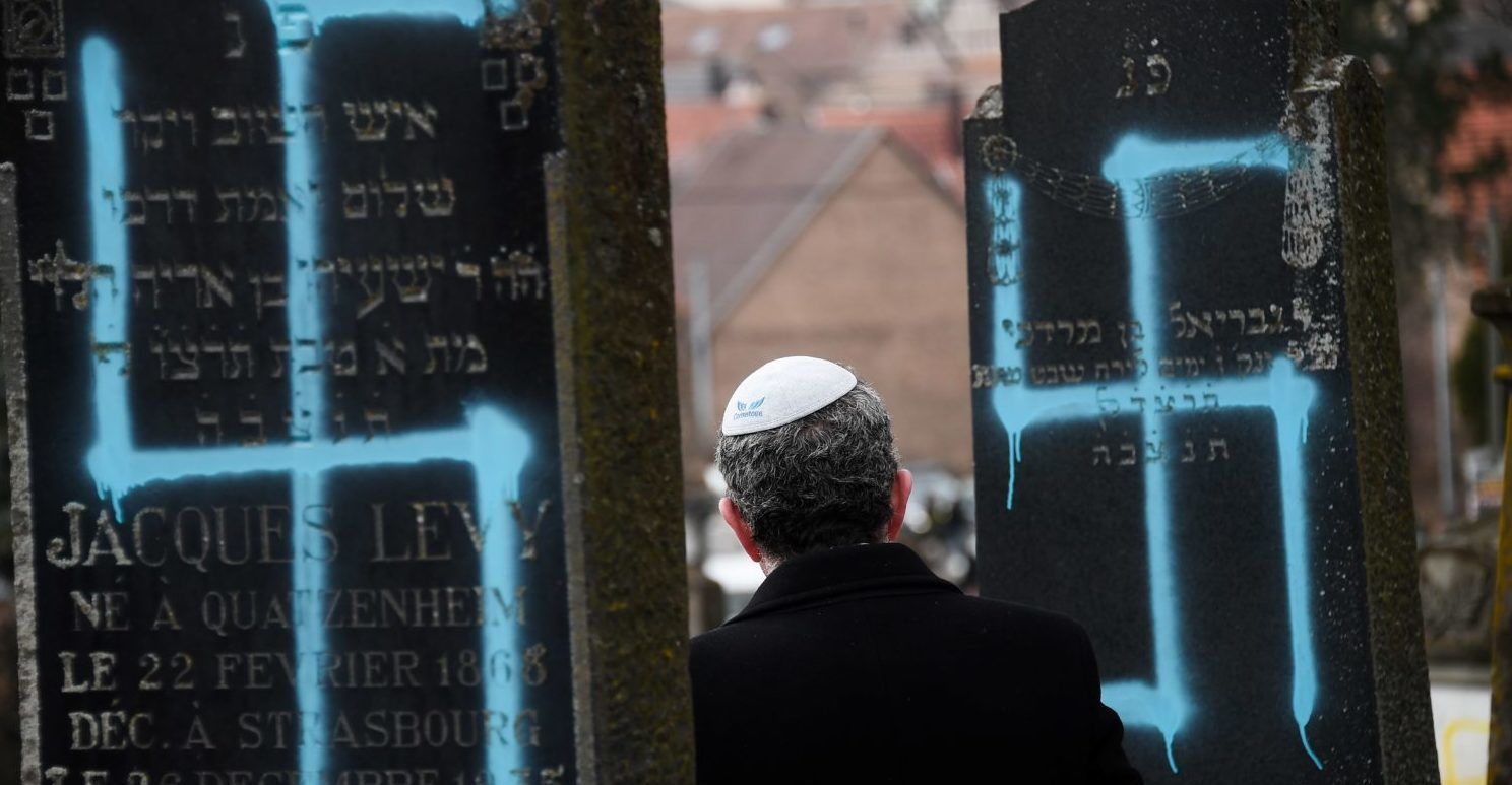 TOPSHOT - A man walks by graves vandalised with swastikas at the Jewish cemetery in Quatzenheim, on February 19, 2019,(FREDERICK FLORIN/AFP/Getty Images)