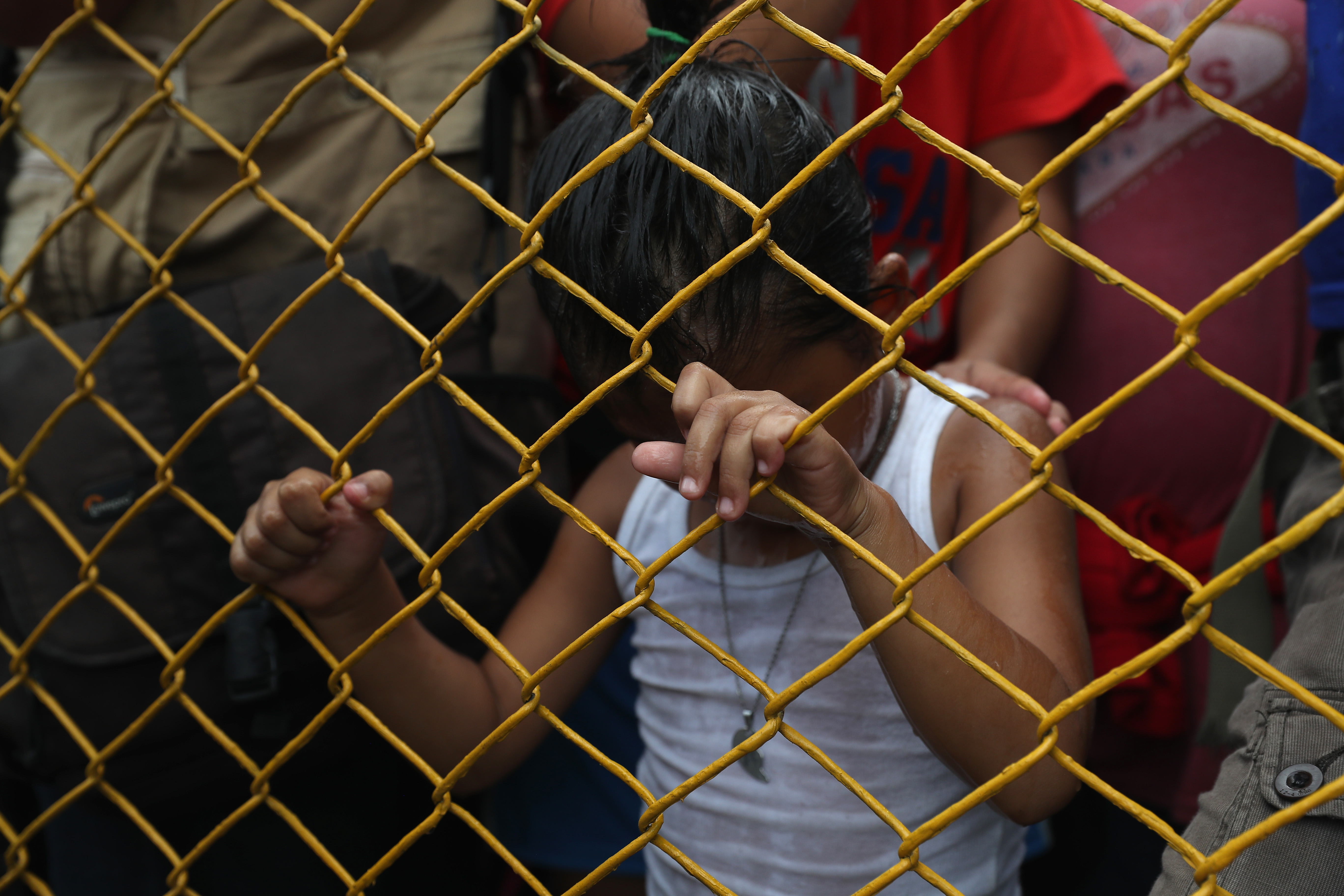 A young member of the immigrant caravan clutches a fence separating Guatemala from Mexico. (Photo by John Moore/Getty Images)
