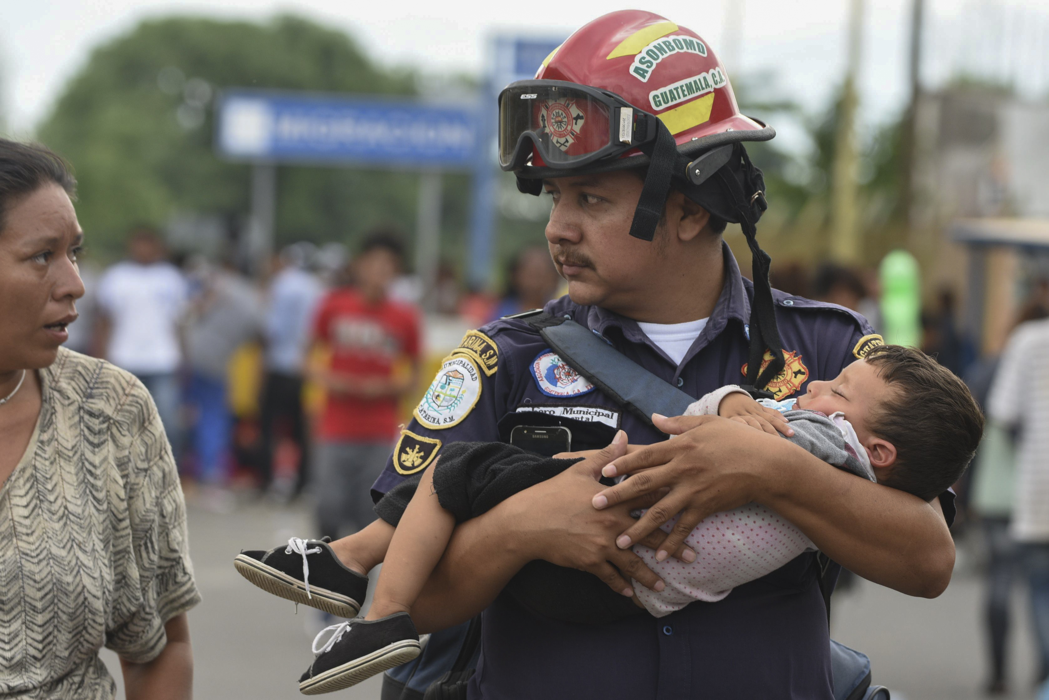 A Guatemalan firefighter carries an ailing baby, as an Honduran migrant caravan heading to the US, reaches the Guatemala-Mexico international bridge ... (Photo by ORLANDO SIERRA / AFP / Getty Images)