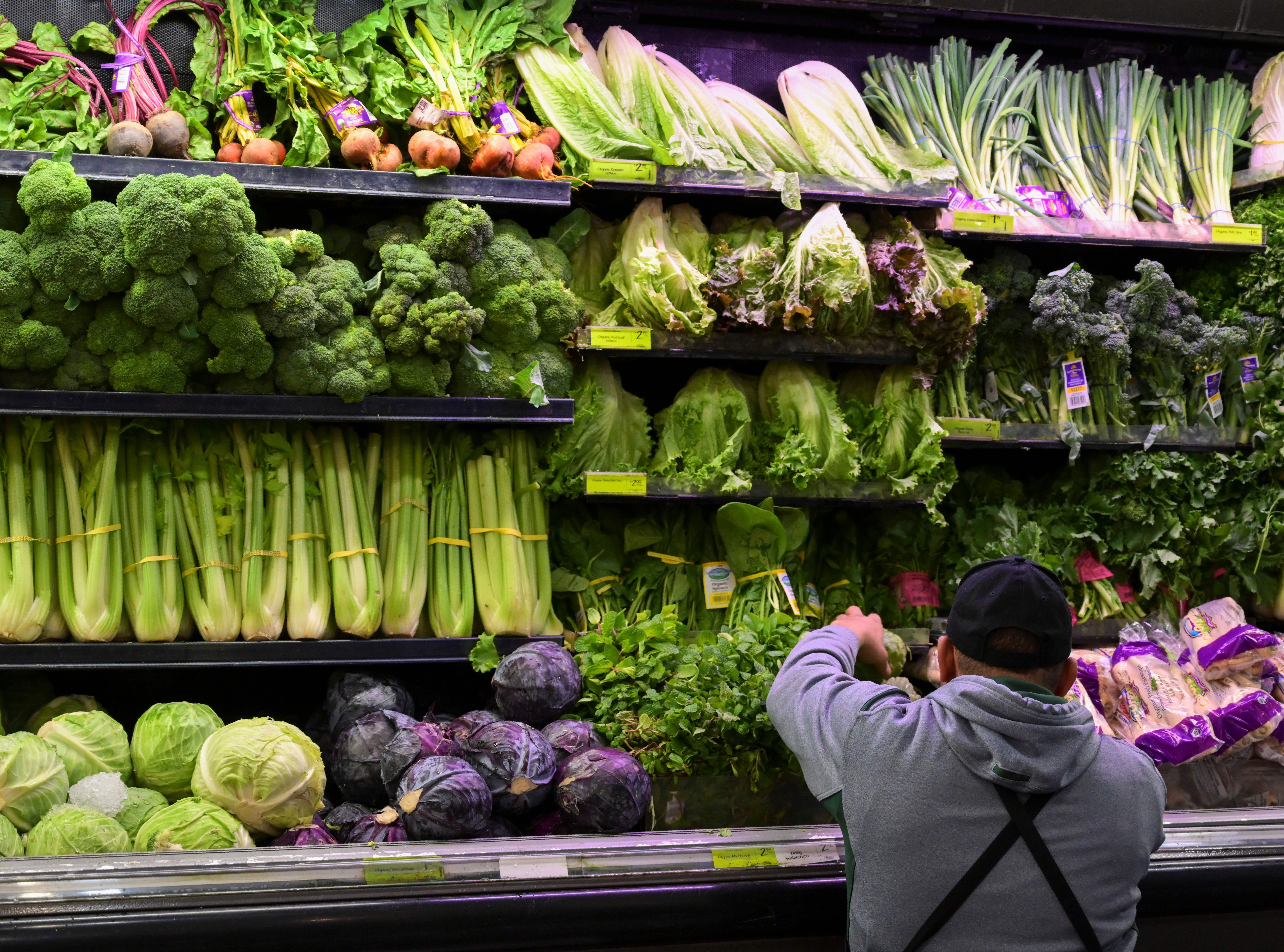 A produce worker stocks shelves near romaine lettuce (top shelf center) at a supermarket in Washington, DC on November 20, 2018. (ANDREW CABALLERO-REYNOLDS/AFP/Getty Images)
