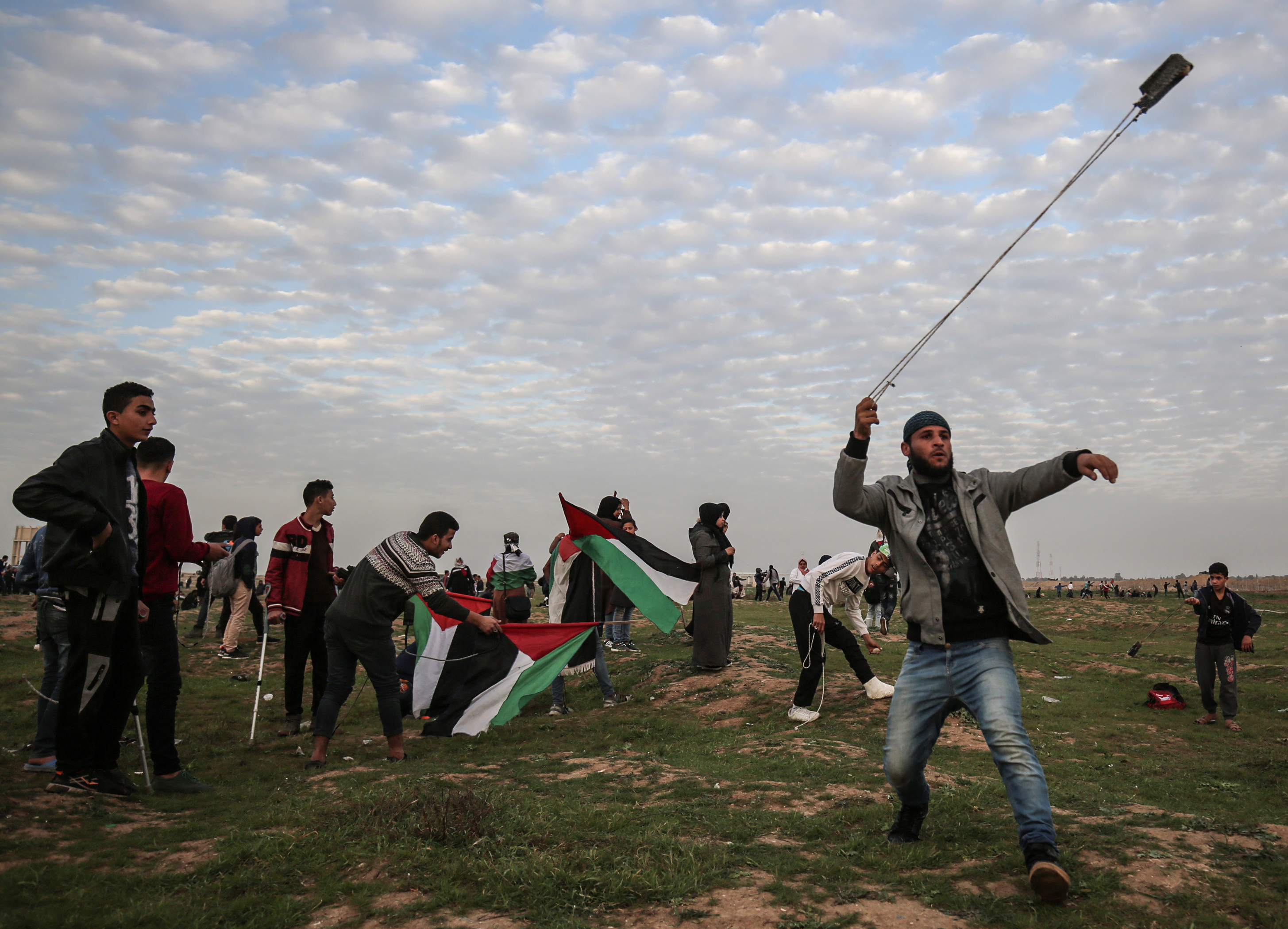 A Palestinian protester uses a slingshot to hurl rocks at Israeli troops as others carry national flags during a demonstration near the fence along the border with Israel east of Gaza City