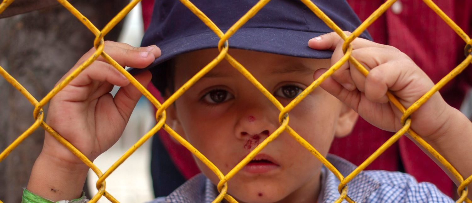 A Honduran migrant boy looks thorugh the fence of a warehouse used as shelter in Piedras Negras, Coahuila, Mexico, in teh border with the US on February 14, 2019. - Around 1,700 migrants traveling in caravan reached the US-Mexican border last week. (Photo by CESAR AGUILAR/AFP/Getty Images)