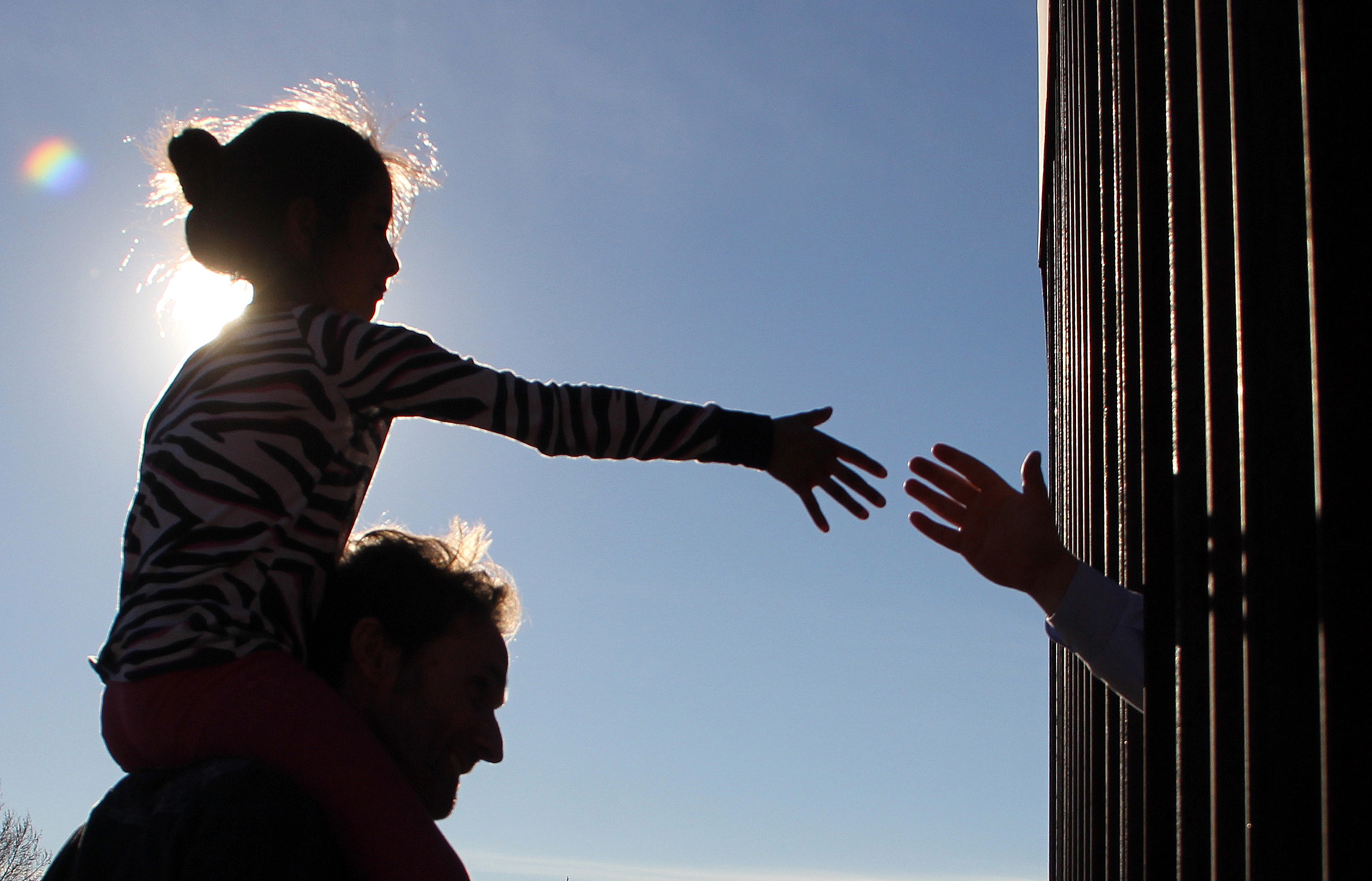 A girl from Anapra, a neighbourhood on the outskirts of Ciudad Juarez in Mexico, touches hands with a person on the United States through the border fence, during a prayer with priests and bishops from both countries to ask for the migrants and people of the area, on February 26, 2019. - Built two years ago, the Anapra fence is one of several reinforced border barriers that the administration of US President Donald Trump calls the first sections of the wall. (Photo by Herika MARTINEZ / AFP) (Photo credit should read HERIKA MARTINEZ/AFP/Getty Images)