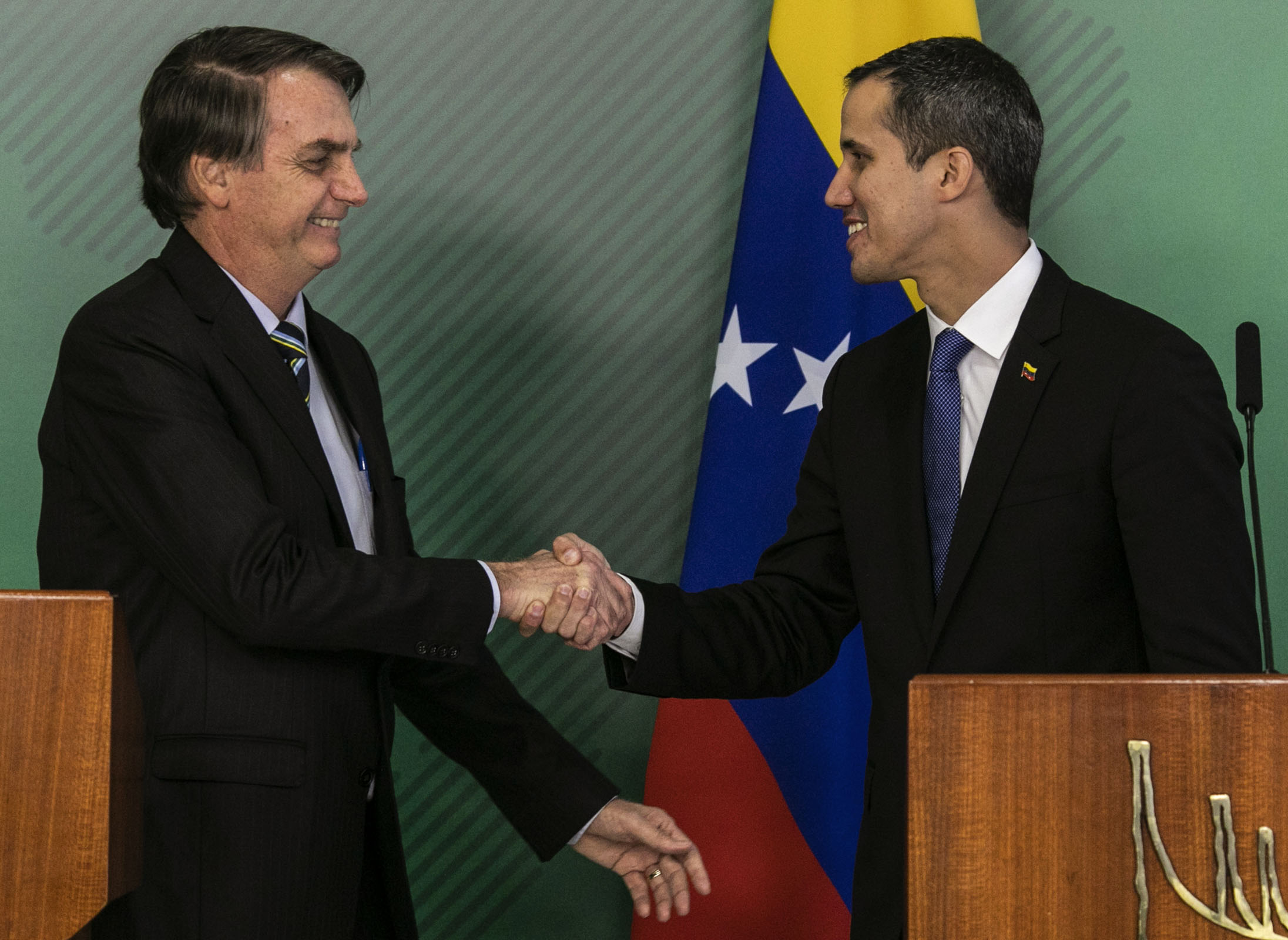 Brazil's President Jair Bolsonaro (L) and Venezuelan opposition leader and self-declared acting president Juan Guaido shake hands during a joint press conference after holding a meeting at Planalto palace in Brasilia on February 28, 2019. (SERGIO LIMA/AFP/Getty Images)