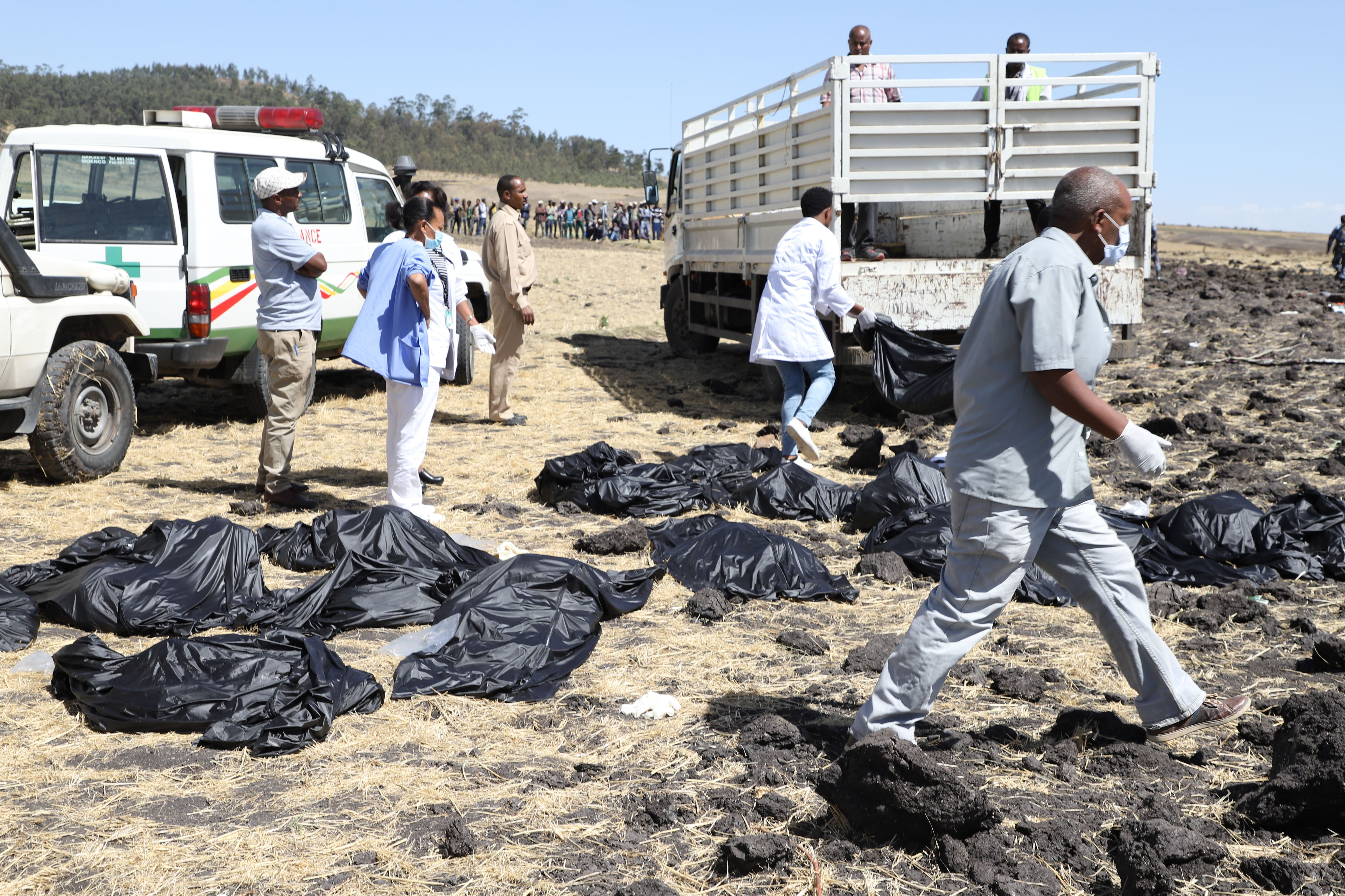 Rescue team walk past collected bodies in bags at the crash site of Ethiopia Airlines (MICHAEL TEWELDE/AFP/Getty Images)
