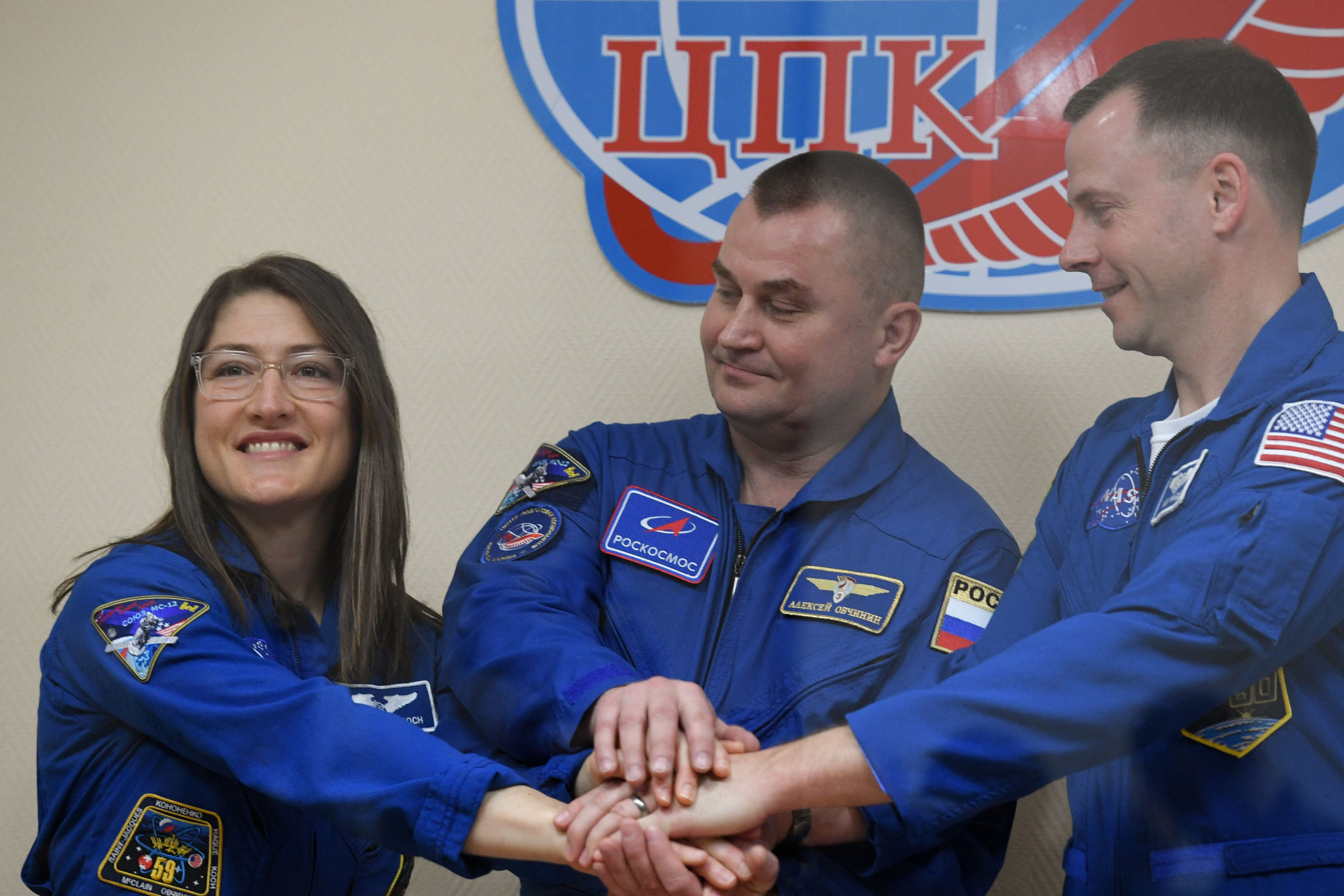 Members of the International Space Station (ISS) expedition 59/60, NASA astronauts Christina Hammock Koch (L) and Nick Hague (R) and Russian cosmonaut Alexey Ovchinin, pose at the end of a press conference at the Russian-leased Baikonur cosmodrome in Kazakhstan on March 13, 2019. (KIRILL KUDRYAVTSEV/AFP/Getty Images)