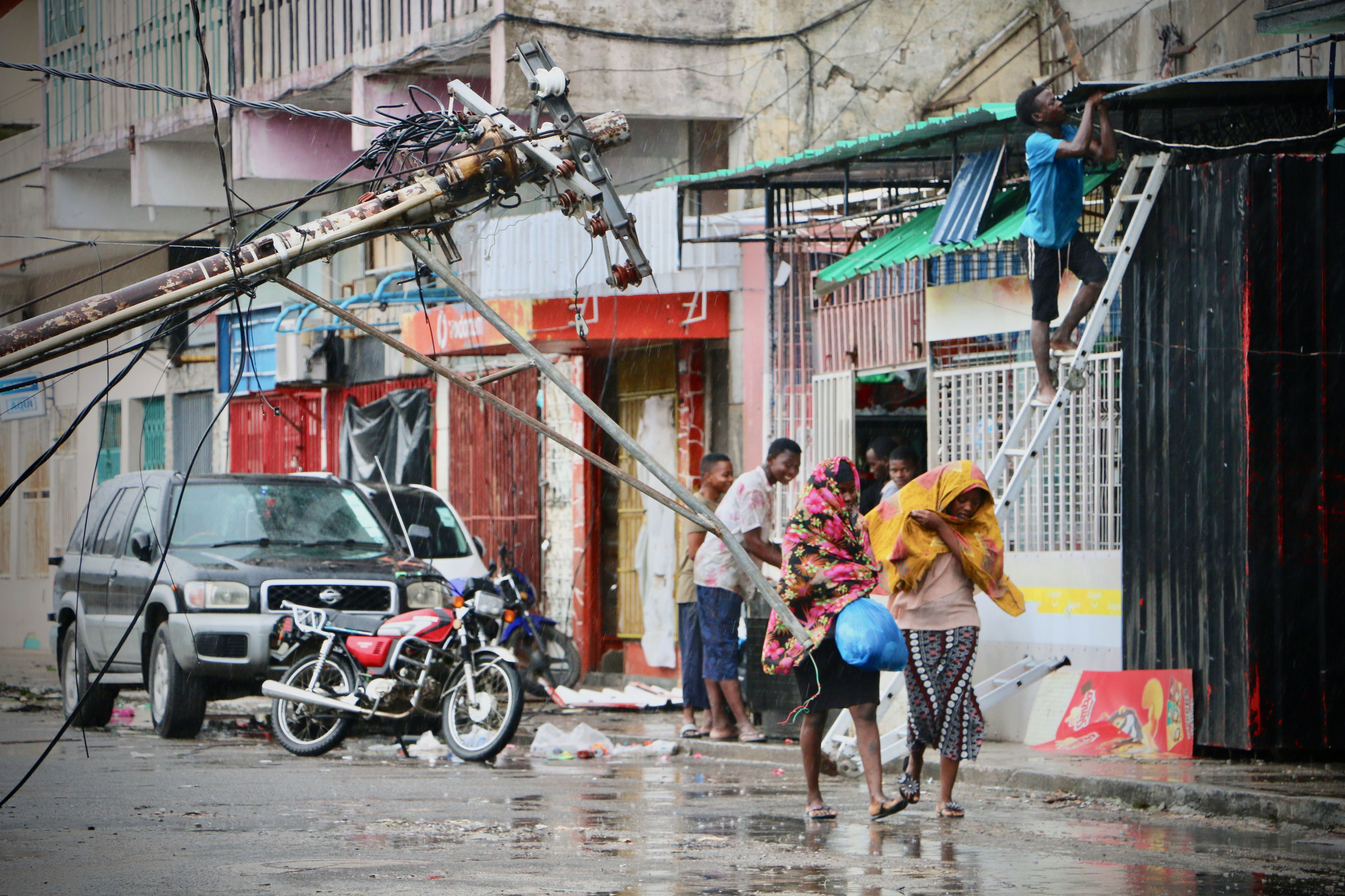 Residents are seen protecting themselves by the rain in the aftermath of the passage of the cyclone Idai in Beira, Mozambique, on March 17, 2019. (ADRIEN BARBIER/AFP/Getty Images)