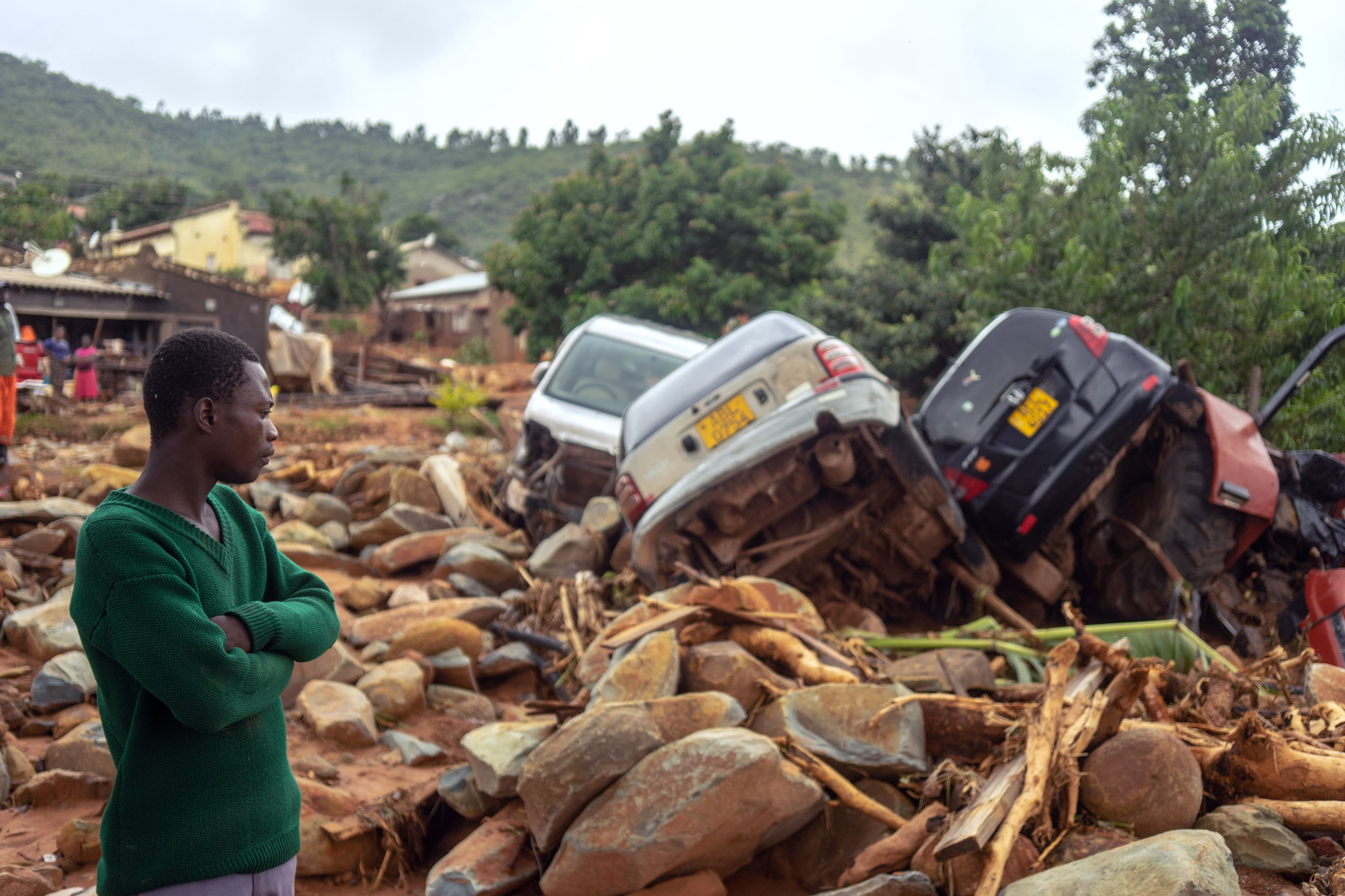 A man stands next to the wreckage a vehicles washed away on March 18, 2019 in Chimanimani, eastern Zimbabwe, after the area was hit by the cyclone Idai. (ZINYANGE AUNTONY/AFP/Getty Images)