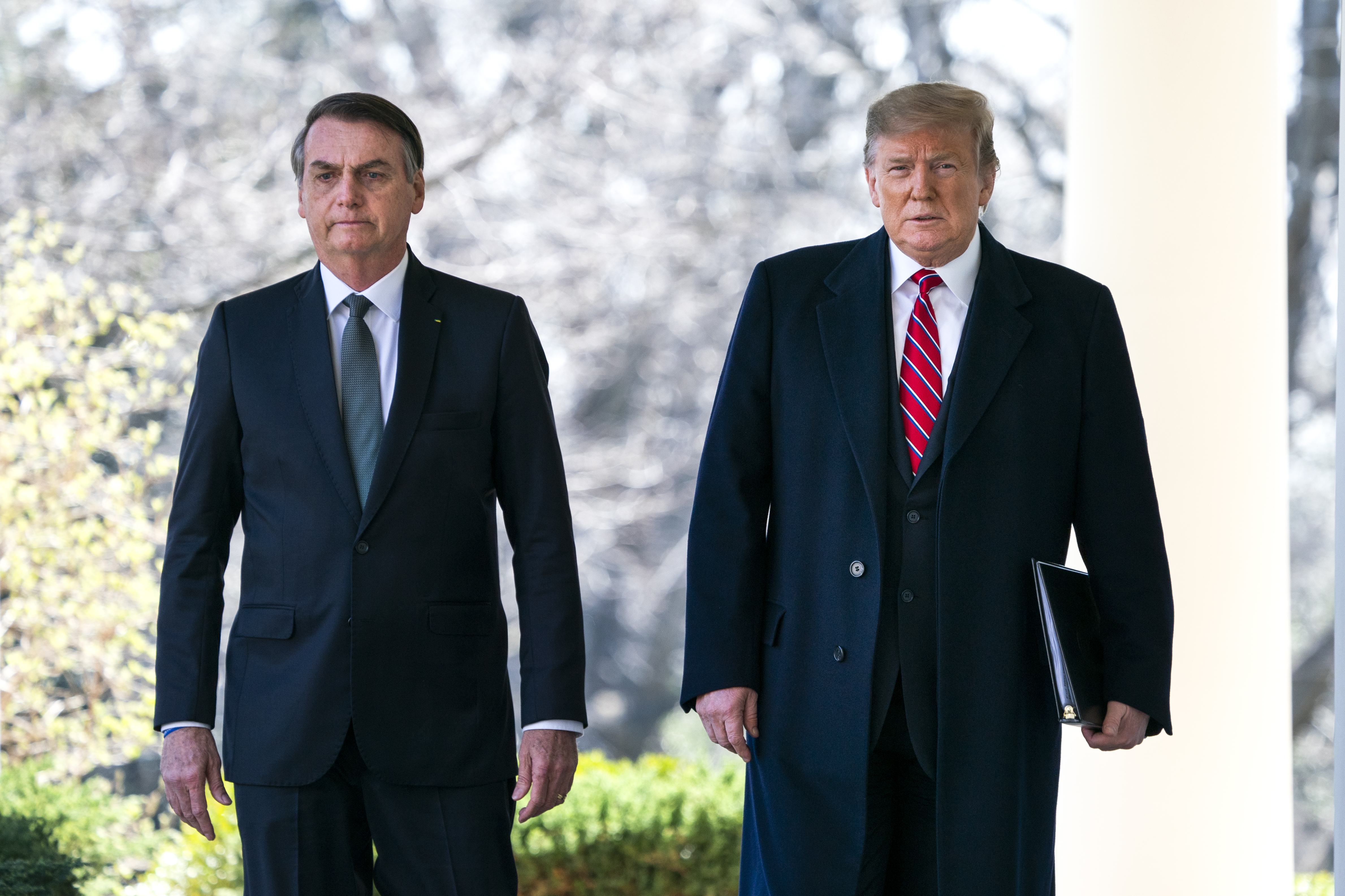 US President Donald Trump (R) and Brazilian President Jair Bolsonaro (L) walk down the Colonnade before a press conference at the Rose Garden of the White House March 19, 2019 in Washington, DC. (Photo by Jim Lo Scalzo-Pool via Getty Images)