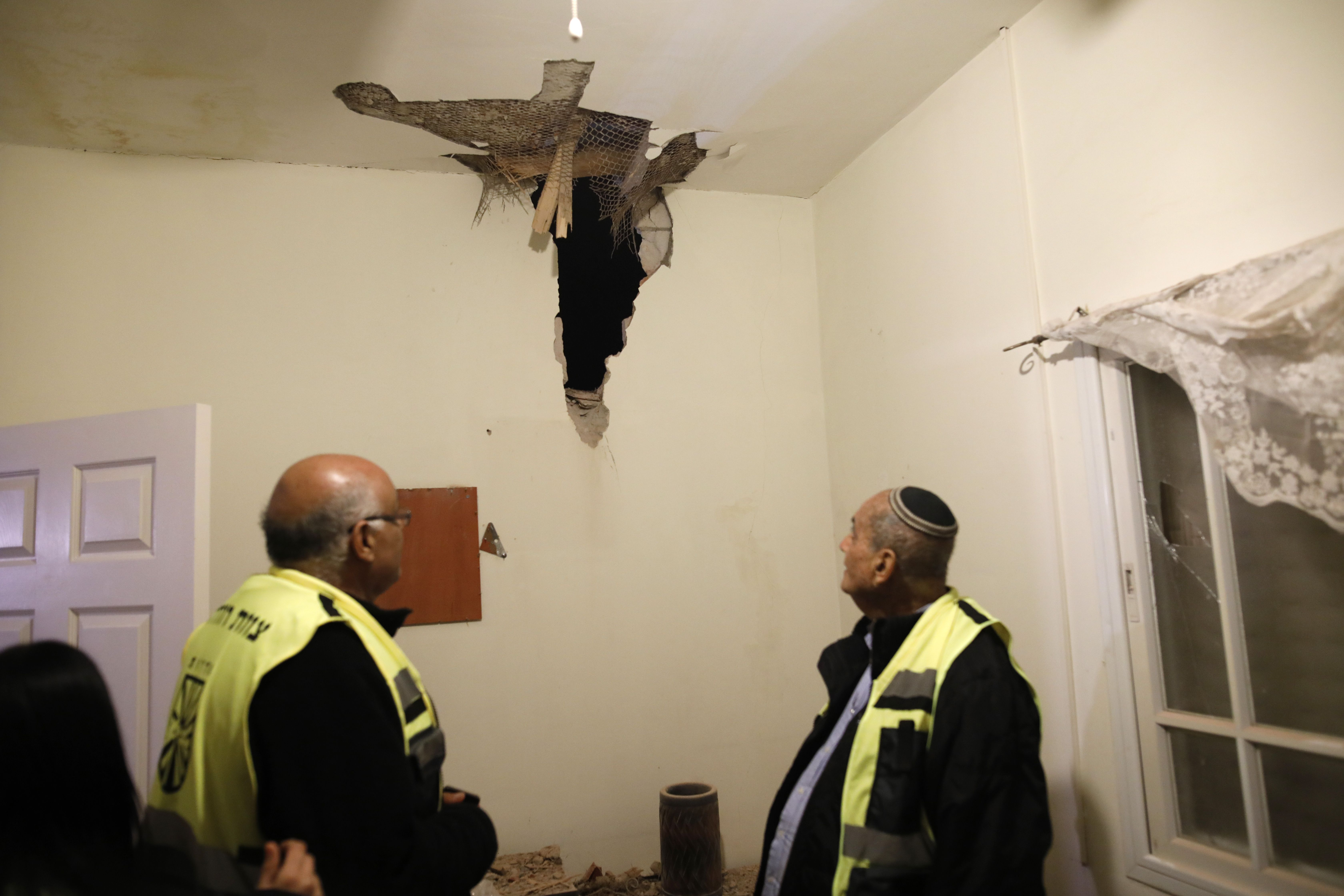 Volunteer rescuers stare at the damage in the ceiling of a house in the southern Israeli town of Sderot, caused by a rocket fired from the Gaza Strip on March 25, 2019. (Photo by Ahmad GHARABLI / AFP)