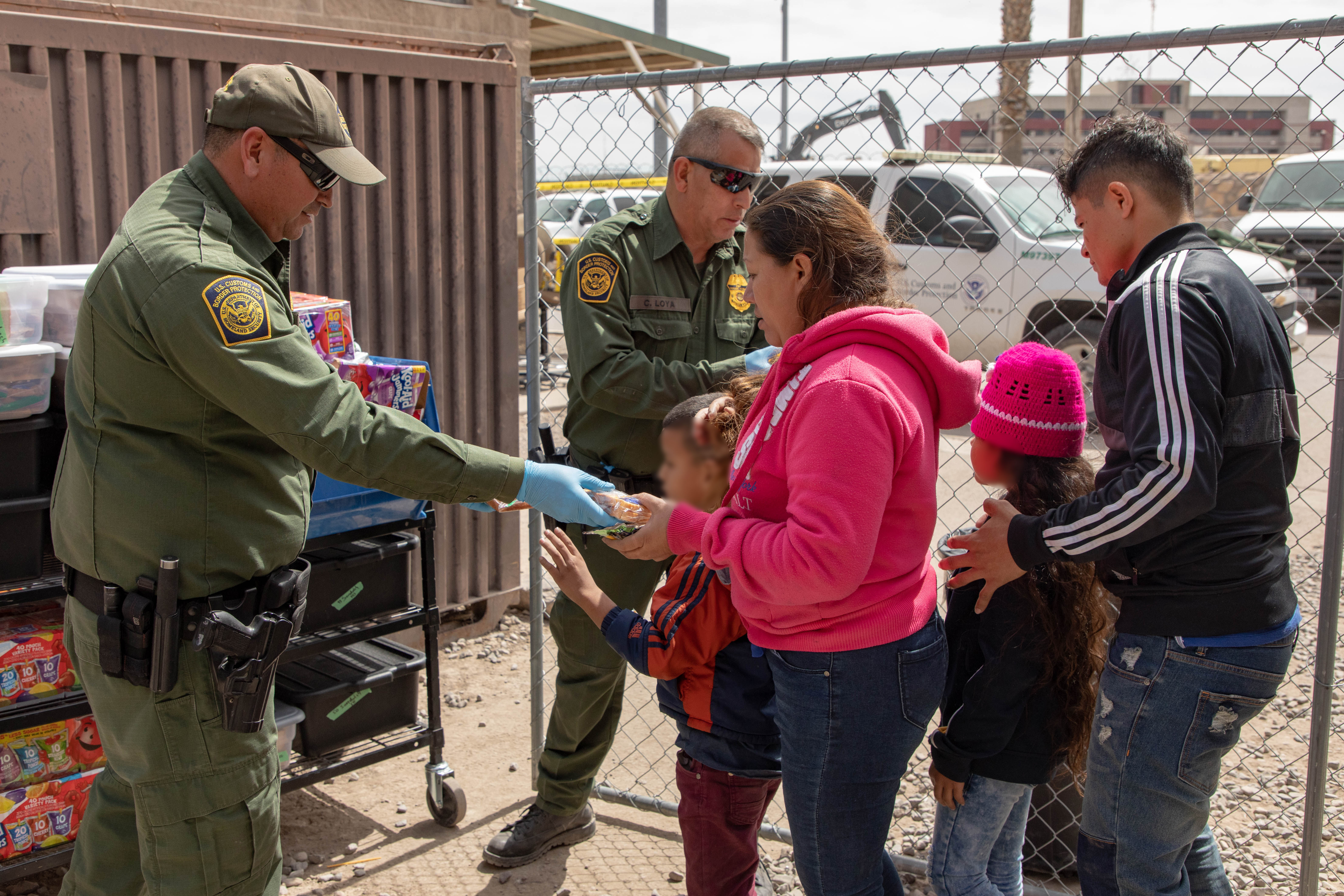 In this handout image provided by the U.S. Customs and Border Protection Office of Public Affairs - Visual Communications Division, after crossing the international border between the United States and Mexico, and surrendering to a border patrol agent, migrants are brought to a processing center where they receive food and water as well as medical attention if needed, on March 22, 2 (Photo by Mani Albrecht/U.S. Customs and Border Protection via Getty Images)