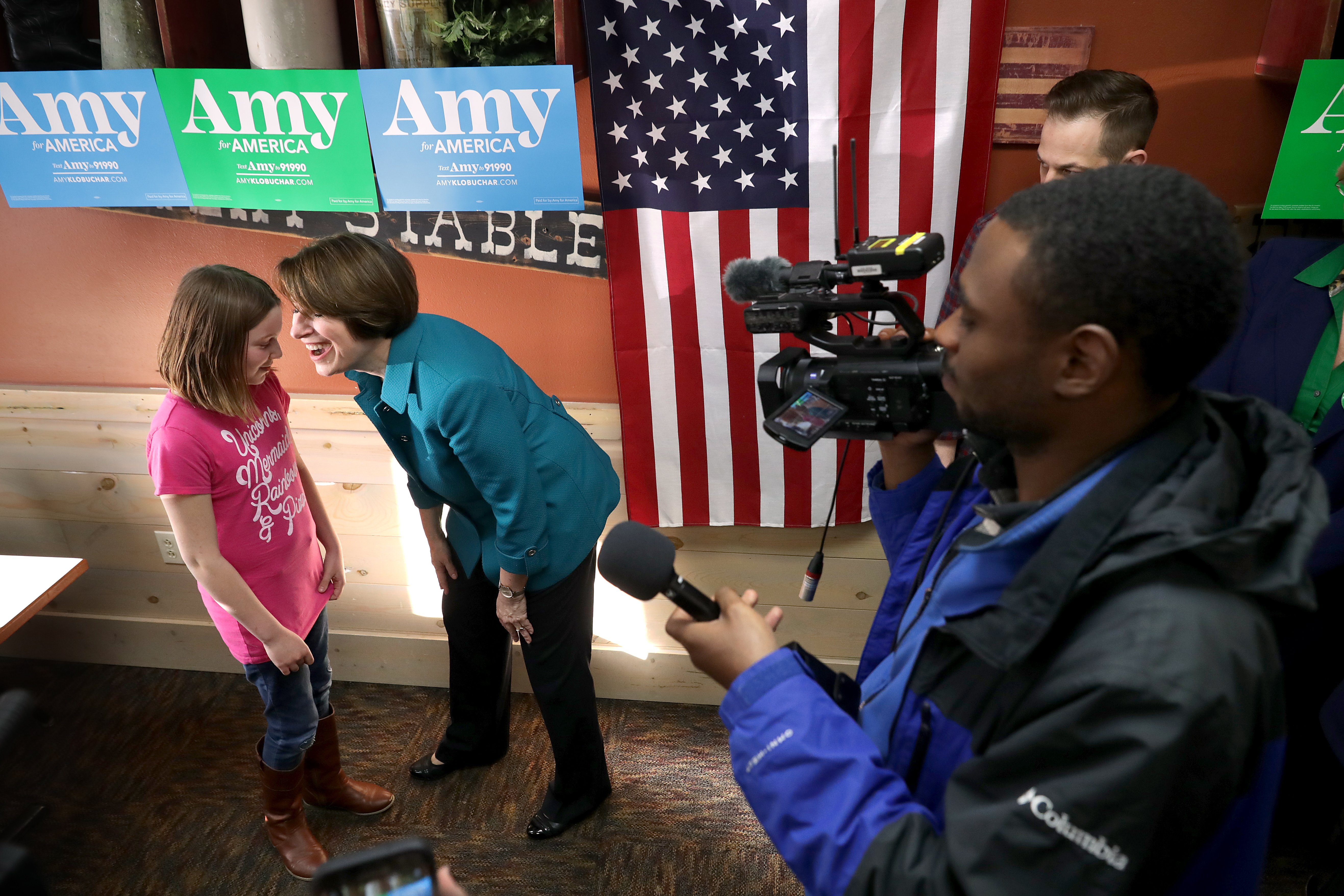 U.S. Sen. Amy Klobuchar asks a girl about her shirt that reads, 'Unicorns, Mermaids, Rainbows & Pizza' while campaigning for the Democratic presidential nomination at the Pizza Ranch restaurant March 16, 2019 in Independence, Iowa. (Photo by Chip Somodevilla/Getty Images)
