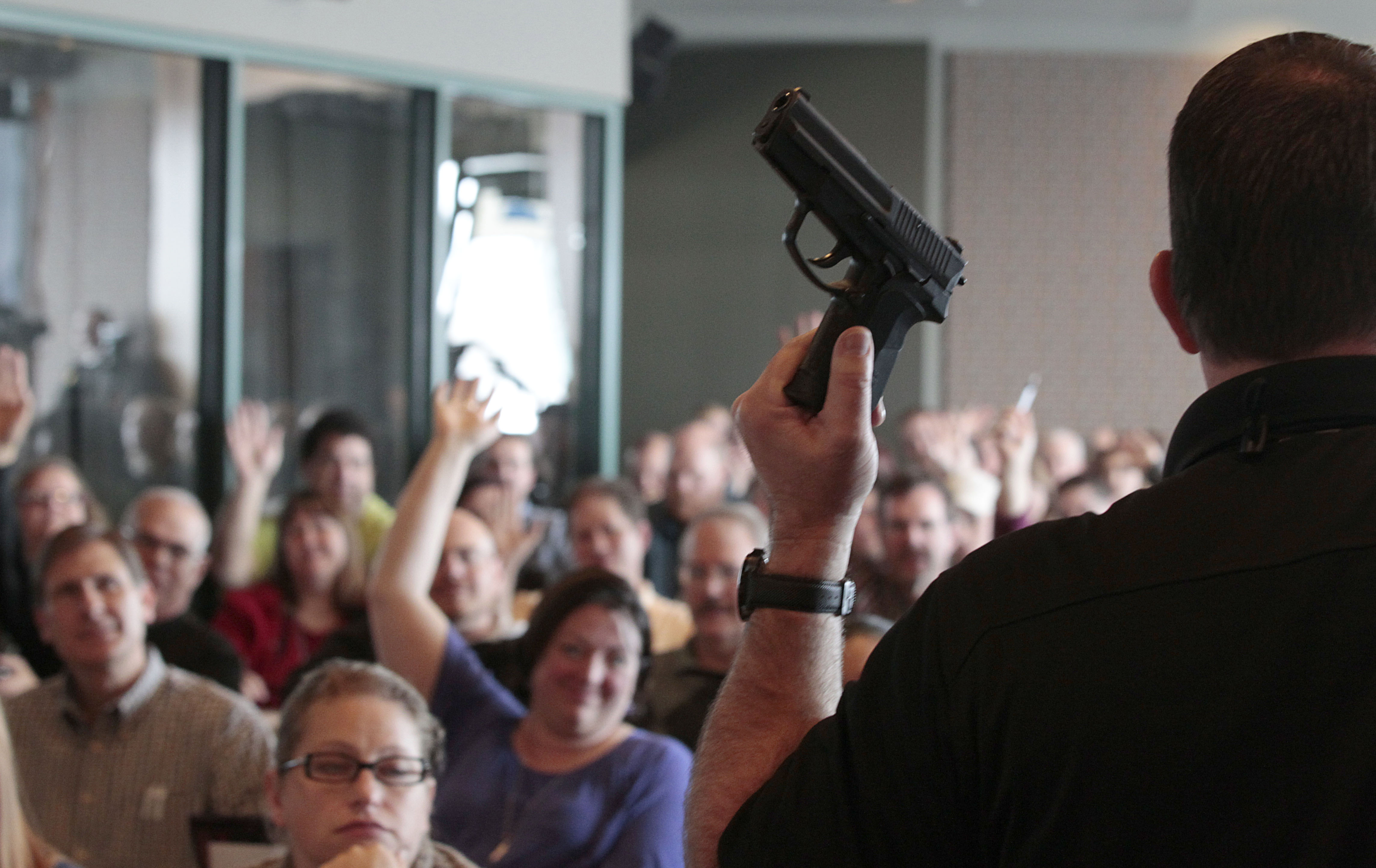 Firearm instructor Clark Aposhian holds a handgun up as he teaches a concealed-weapons training class to 200 Utah teachers ... (Photo by George Frey/Getty Images)