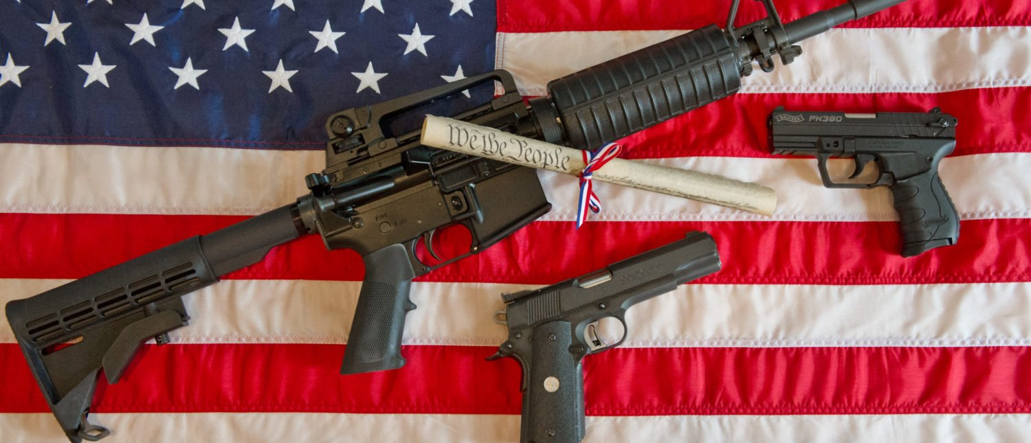 This February 4, 2013 photo illustration in Manassas, Virginia, shows a Colt AR-15 semi-automatic rifle a Colt .45 semi-auto handgun and a Walther PK380 semi-auto handgun and a copy of the US Constitution on top of the American flag. (KAREN BLEIER/AFP/Getty Images)